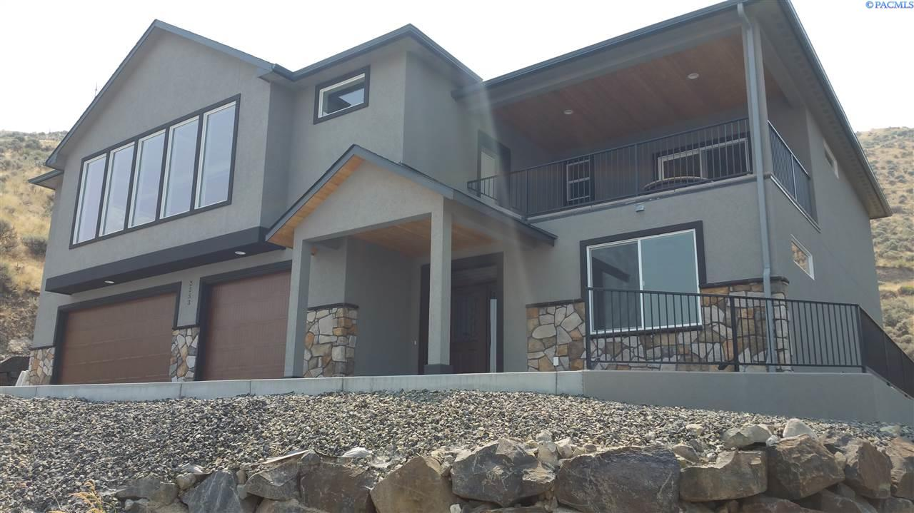 Newly built by StoneCrest Builder's!  In this home, you will enjoy the incredible views of the city lights and the Columbia River spanning from White Bluffs to the Blue Mountains. All in a unique custom designed by the builder to capture all of it.  The builder leveled the lot with a rockery basalt retaining to perch this home on a flat lot and is completely landscaped.  We add character by adding all the owner living areas upstairs.  Stairs?  If you don't want the exercise, jump in the elevator and come up to the wide-open great room & kitchen.  Check out the views from inside or out on the covered patio.  With no exception to every StoneCrest home the master suite is large and the bathroom has a spa like feeling.  So, relax in the 6-ft. tub surrounded in white/gray accented tiles which flow into the walk in shower matching the quartz countertops.  The large master closet has plenty of room.  Also, upstairs is a roomy flex room where you can see views and access the patio. On the ground level are 3 other bedrooms, a full bath, second covered patio and laundry room plus the large 3 car garage. This home is completed and ready for the new owners to step through the doors.
