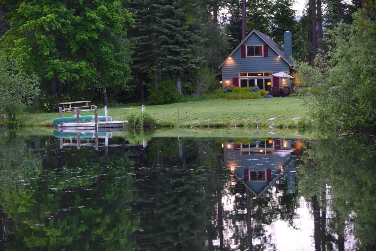 This exceptional property offers a stunning cabin with a picturesque lake view.  This finely crafted mountain cabin includes an open floor plan, custom wood features such as hand hewn beams in living and dining room, black walnut hardwood floors, cedar wainscoting throughout, fir trim around solid wood doors, transom wood windows and French doors opening to a paver patio with pond view. Other exceptional custom features include rock hearth and wood stove, special lighting, built in wood cabinets, tile bathroom and floors, skylights, and master bedroom with pond view.  In addition, this property features elaborate landscaping, outdoor shower, aspen grove, lake flume, boat dock, multiple foot trails/bridges and fruit orchid with mature apple, pear, and cherry trees. Spring Creek meanders through this amazing treed parcel with a 2.5-acre trout lake. The gated paved driveway leads to a large pole structure for vehicles or equipment and storage shed. Expansive irrigation exits throughout the property and lawn areas.  There are several optional building sites for a future or additional home on this spacious heavenly parcel.