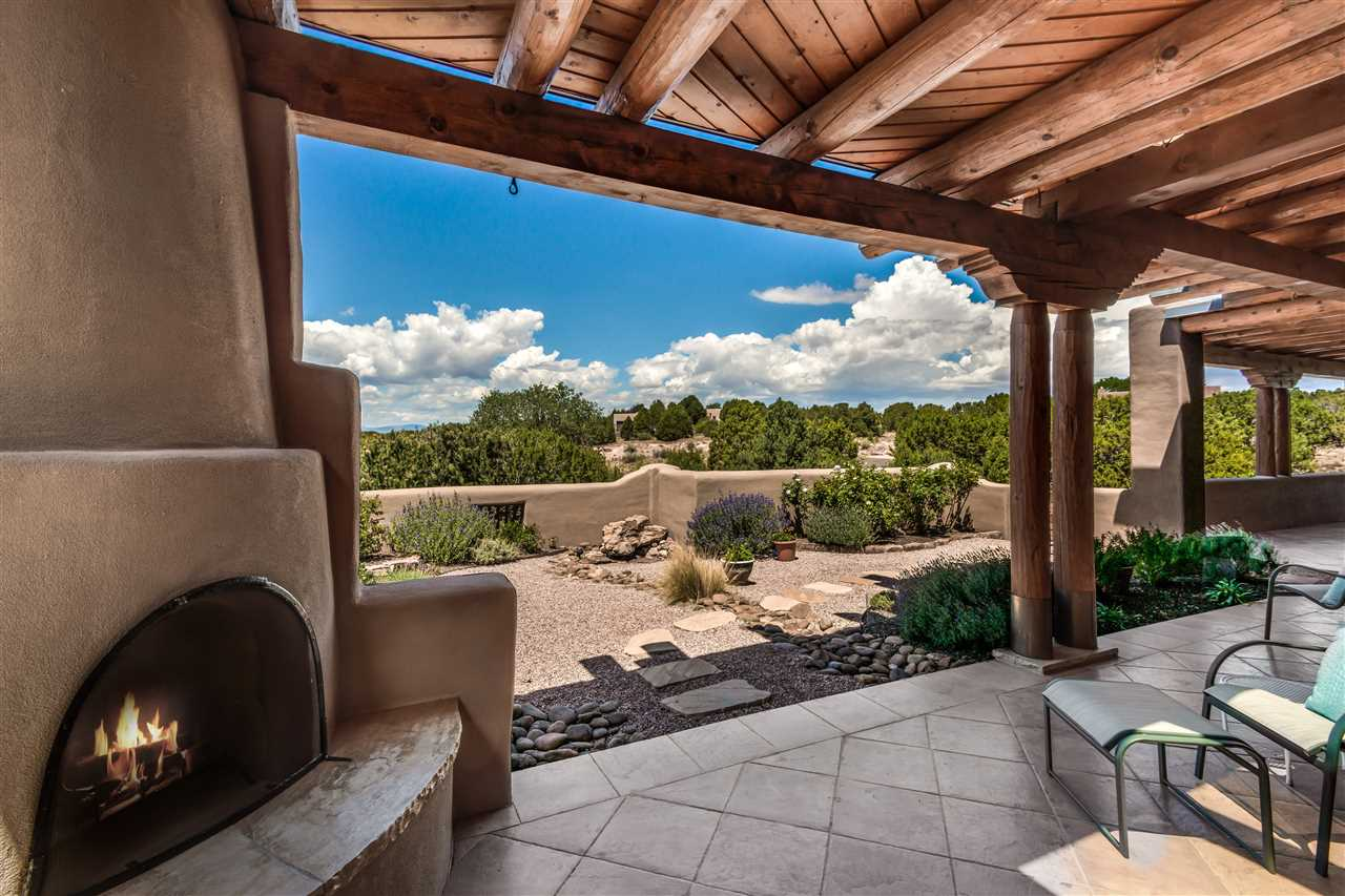 Dramatic Jemez Views from this Gracious Home in gated Las Campanas Estates I, the most sought after location for it's easy drive into town.  Constructed by renowned Builder Michael Kern on 1.7 acres, Open Concept Home includes 3 Bedrooms, 3.5 Baths, Family Room & 3-Car Garage.  Welcoming private entry courtyard offers extensive landscaping & soothing water feature. Living/Dining accesses a spacious back portal with Jemez views, wood-burning Kiva Fireplace, fountain & built-in BBQ – Perfect for entertaining.  Family Room transitions into the Gourmet Kitchen, with granite counters, large island, Wolf Range/Oven, Warming Drawer, Microwave, Sub-Zero refrigerator, wine cooler & ice maker. Generously-sized Master has a corner Kiva fireplace, spacious walk-in closet, double sinks, large shower & whirlpool tub.  Notable features include 4 fireplaces, 2 water features, central refrigerated A/C throughout the house as well as coved ceilings in the Living, Dining, Kitchen & Family Room.