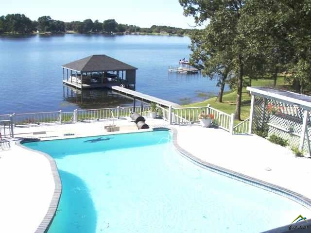 Rare opportunity to own this spectacular waterfront home on Beautiful Lake Bob Sandlin.  5 Level Home with 5 living areas, 4 bedrooms, 5 baths, 2 half baths, swimming pool with sit down area and table, 5 enclosed garages and 2 car porta' cache, 3 stall boathouse & storage building.  Master suite has his/her bathroom, sitting area & 6 closets.  Kitchen has been updated with new flooring and stainless steel appliances, attached living area has new carpet and paint.  New carpet and paint in downstairs gameroom.  Many, Many Extras!!!
