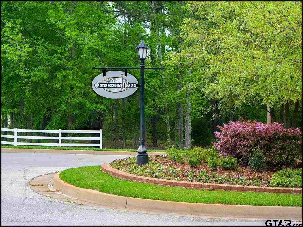 Beautiful Estate Lot in Charming Charleston Park. Build your dream home on this wooded .713 acre lot in this unique community, in walking distance to UT Tyler. Architectural styles reminiscent of Charleston, South Carolina style row houses, each homes is unique with inviting front porches and stoops.  Iron lampposts light sidewalks in the evenings for walks before dinner.  Enjoy the community pool in summer, too. Charleston Park is one-of-a-kind in Tyler, isn't it time to slow down enough to savor your home?