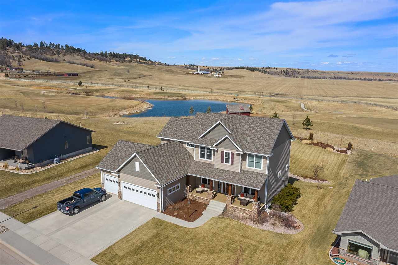 Escape to this luxurious golf course home located on Elkhorn Ridge Golf Estates and enjoy the beauty of the Black Hills. Located within minutes to Spearfish, Deadwood, or Sturgis this Signature home has 5 beds and 4.5 baths with magnificent views out of every window. Upon entering you are welcomed by an open living area, a spacious kitchen, formal dining area, and cozy fireplace. Enjoy everything the basement has to offer with a finished wet bar, workout room, and spacious living area, a bathroom and a guest bedroom. This home also has a large mud room coming off of the finished 3 stall heated garage and a laundry room conveniently located upstairs next to the bedrooms. Start your day at the main floor office while taking in panoramic views of the Black Hills and Terry Peak and end it on the covered front porch or back deck while enjoying the peaceful countryside and adjacent pond with abundant wildlife. Listed by Jeffrey Christians, Keller Williams Black Hills 605-340-0768.