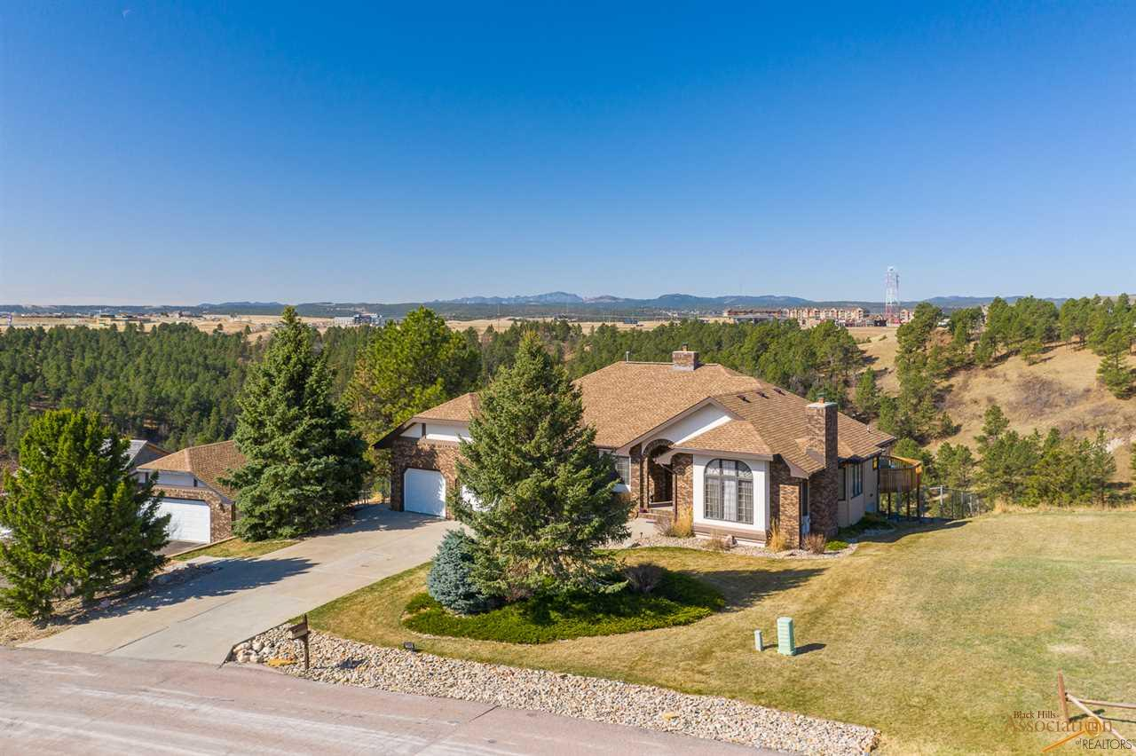 Listed by Jeremy Kahler, KWBH, 605-381-7500.  Welcome home to this sprawling Tudor Style Ranch with walkout lower level, nestled on 1.38 acres with beautiful views! *Smart home updates- 2 furnaces, 1 humidifier, 2 septics, surround sound and a new impact resistant roof (2020) *6 bedrooms and 3 bathrooms *Sunken front sitting room with a gas fireplace and arched casement windows *Formal dining area with trayed ceilings *Gourmet kitchen with ceiling height cabinetry with crown molding, granite countertops, glass tile backsplash, a kitchen island, stainless steel Kitchenaid appliance suite (including double ovens, a 5-burner gas range and microwave drawer) and cozy breakfast nook *Spacious living room with vaulted ceilings and a 2nd gas fireplace *Main level laundry room *3 bedrooms, an office and 2 bathrooms on main level *Main level master suite in back of home, with a large bedroom with private deck access, walk in closet and ensuite bath with custom tile walk in shower and jet tub