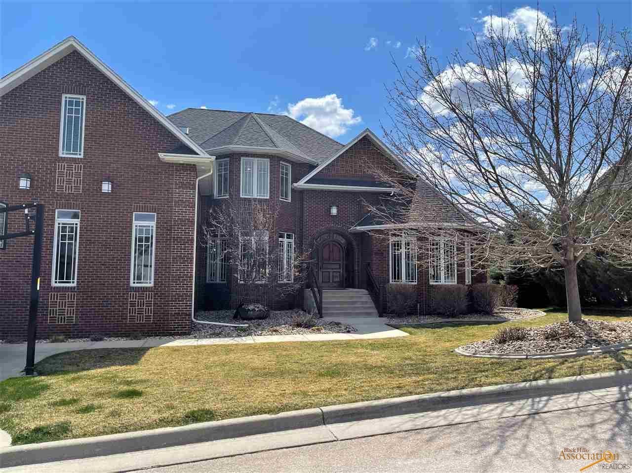 STUNNING HOME with VIEWS & PRIVACY! Listed by Jennifer Landguth, Hegg Realtors, Inc. 6053818273. This high quality, all brick home with gorgeous views has it all including 6 bedroom suites, a formal dining room, billiard room, 2 story family room with fireplace, a main level laundry/mudroom & 1/2 bath near the large kitchen & nook with views & deck access. There is also a main level master bedroom suite featuring a sitting area, tray ceilings, French doors to the deck, a large bathroom w/ tub & steam shower, private toilet, double sinks & a large walk in closet. The open stairway leads to the upper level complete with 3 bedroom suites & bonus room perfect for family times or a quiet office space.  The lower level features high ceilings, a media room, bar with dishwasher, card room, party bath, family room, wine room, 2 bedroom suites & patio access. The 3 car garage has high ceilings perfect for a car lift! So many amenities - a must see!
