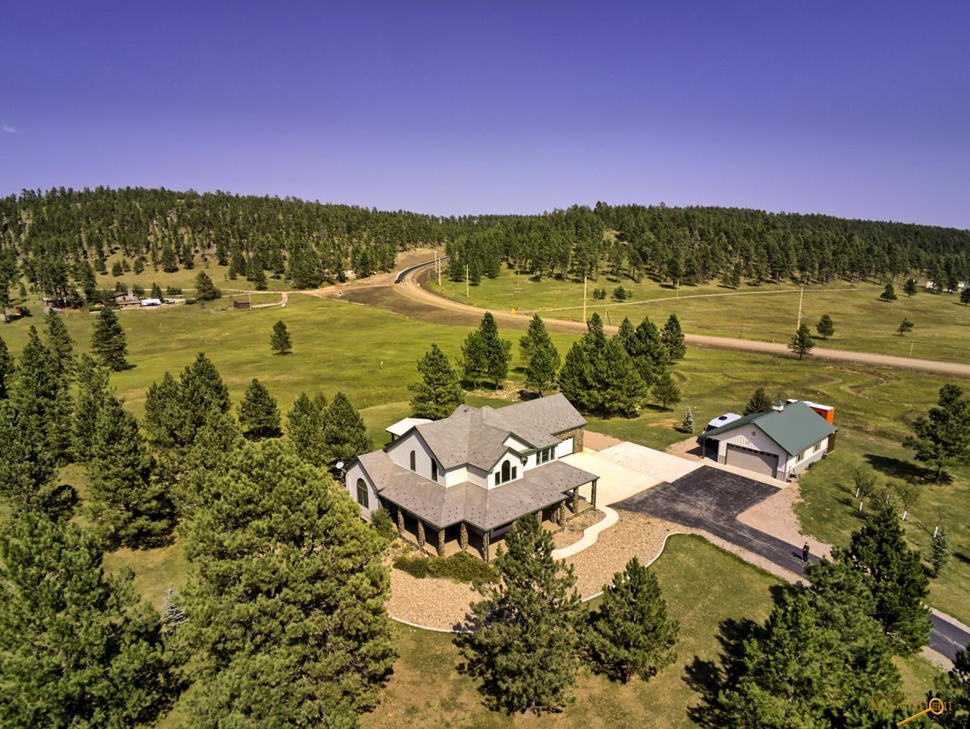 Welcome home to this spectacular retreat that's only minutes from Rapid City but offers all of the serenity that the Black Hills has to offer! Beautiful views in all directions can be taken in from the covered wrap around front porch. Entertain a large group with ease under the huge covered back patio or ride your horse to the adjacent National Forest Service from this horse friendly property! The inside of this house is remarkable too! A two story living room is the centerpiece of the home surrounded by the well appointed kitchen with breakfast nook, formal dining, large master suite with travertine tiled floors and shower and walk-in closet, laundry, powder room and state of the art theatre room that will make everyone want to see the big game at your place. Upstairs has two nice sized bedrooms and a guest bath and the basement offers a huge family room, workout room, bedroom and another bath. Both attached and detached garages are insulated and heated.
