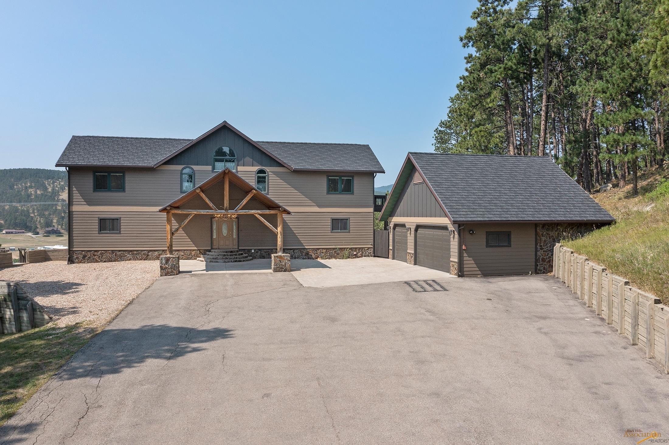 Breath taking views of the Black Hills from this 5784 sq ft Home which is nestled on 6.8 acres, high on the hill and borders U.S. B.L.M. property. Home includes 5 large bedrooms, 4 full bathrooms, main floor living room with gas fire place, built in we bar, walk-in coat closet, walk-in pantry as well as a huge laundry room.  The 3 car garage is heated and encompassed by paved parking for multiple vehicles with two 50 amp RV hookups. Need more garage/shop space? There's plenty of room to build more.  Enjoy your evenings in the Hot Tub of entertaining guests on the large deck. This Home is Move in Ready.
