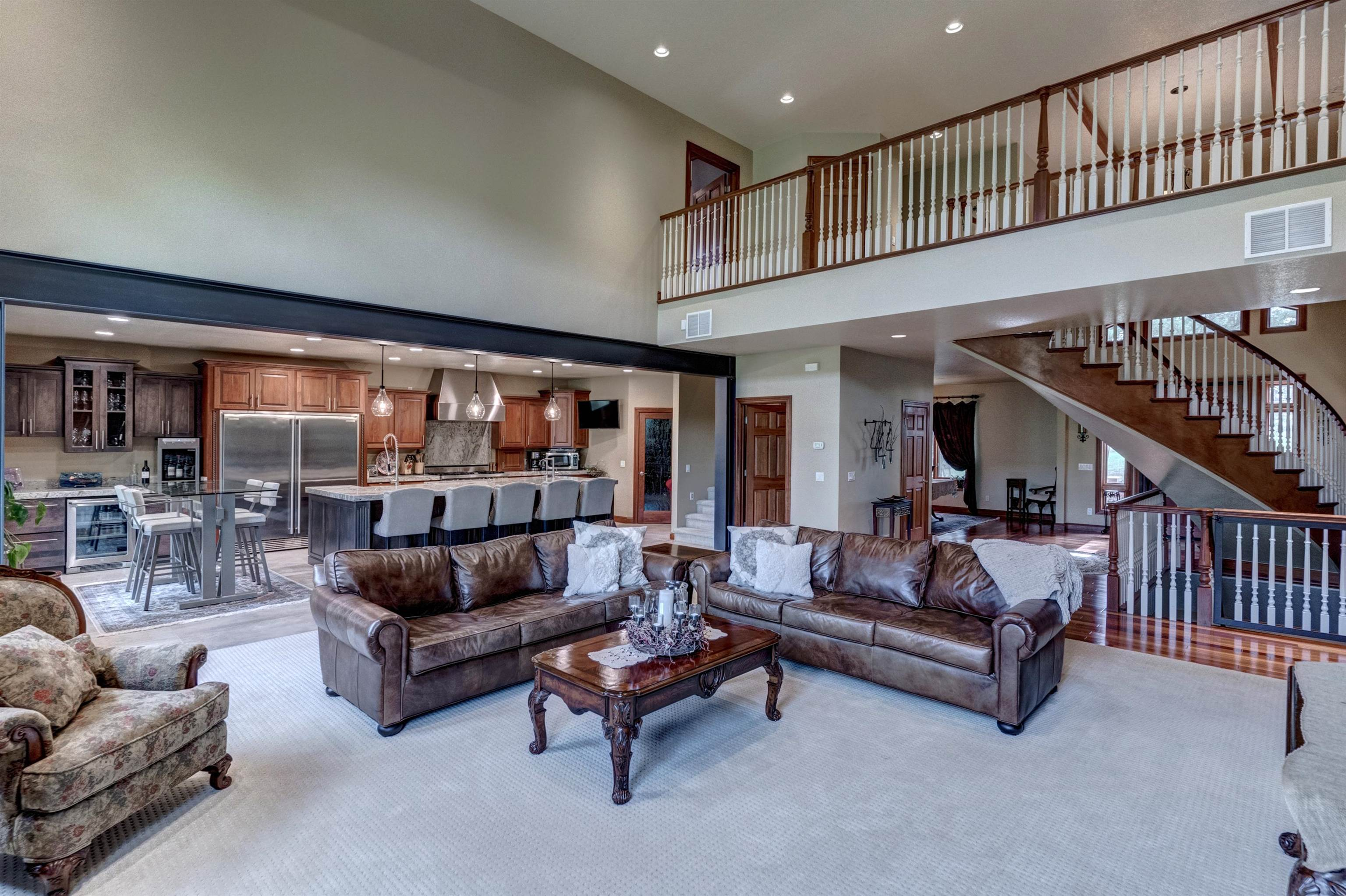 Listed by Lori Barnett at VIP Properties, 605-786-5817.  Luxury living only minutes from Rapid City!  This 5500+ square foot home is nestled on 7 treed acres off of Rimrock Hwy.  A winding custom staircase greets you at the door and ushers you into an expansive great room & kitchen which is perfect for entertaining!  A massive island is the centerpiece of the kitchen which includes a wine bar area, large pantry, & granite countertops to round out this gourmet kitchen.  Off of the kitchen is a large deck with fireplace & wood fueled pizza oven.  The main level also offers a formal dining room, office, half bath, & large laundry room.  The upper level can be accessed by the main staircase or by an additional flight that is off the kitchen.  The walkway is open to the living room & is flanked on one side by the large master bedroom & bath (which includes a jet tub, steam shower, & private deck).  The opposite side of the open walk way offers 2 additional bedrooms with a shared bath.