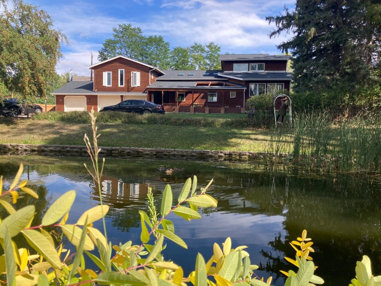 Listed by, Bobby Sundby 209-2777 and Kathy Sundby, SUN REAL ESTATE 484-0422.  Great convenient location close to Arrowhead Golf Course.  Large lot with tons of privacy, mature trees and pond in the front yard for wildlife viewing.City has easement for the pond & the pond is maintained by the City. This home has 4 bedrooms, 4 baths, 3 car garage and is over 5000 sq. ft. Kitchen is perfect for entertaining with an open concept, quartz countertops, and an extra-large 10'x4' island. The living room includes 18ft+ vaulted ceiling, loft area, floor to ceiling bookshelves and panoramic Pella windows. The upstairs includes 3 beds/ 2 baths. The 4th bedroom is separate for a great guest room or office. This home includes tons of at-home entertainment options including a theater room and gym/rec room. The backyard is fenced with a shed, garden boxes, and large deck. New shingles in 2020, updated engineered bamboo flooring in main rooms, and new carpet upstairs/ basement.