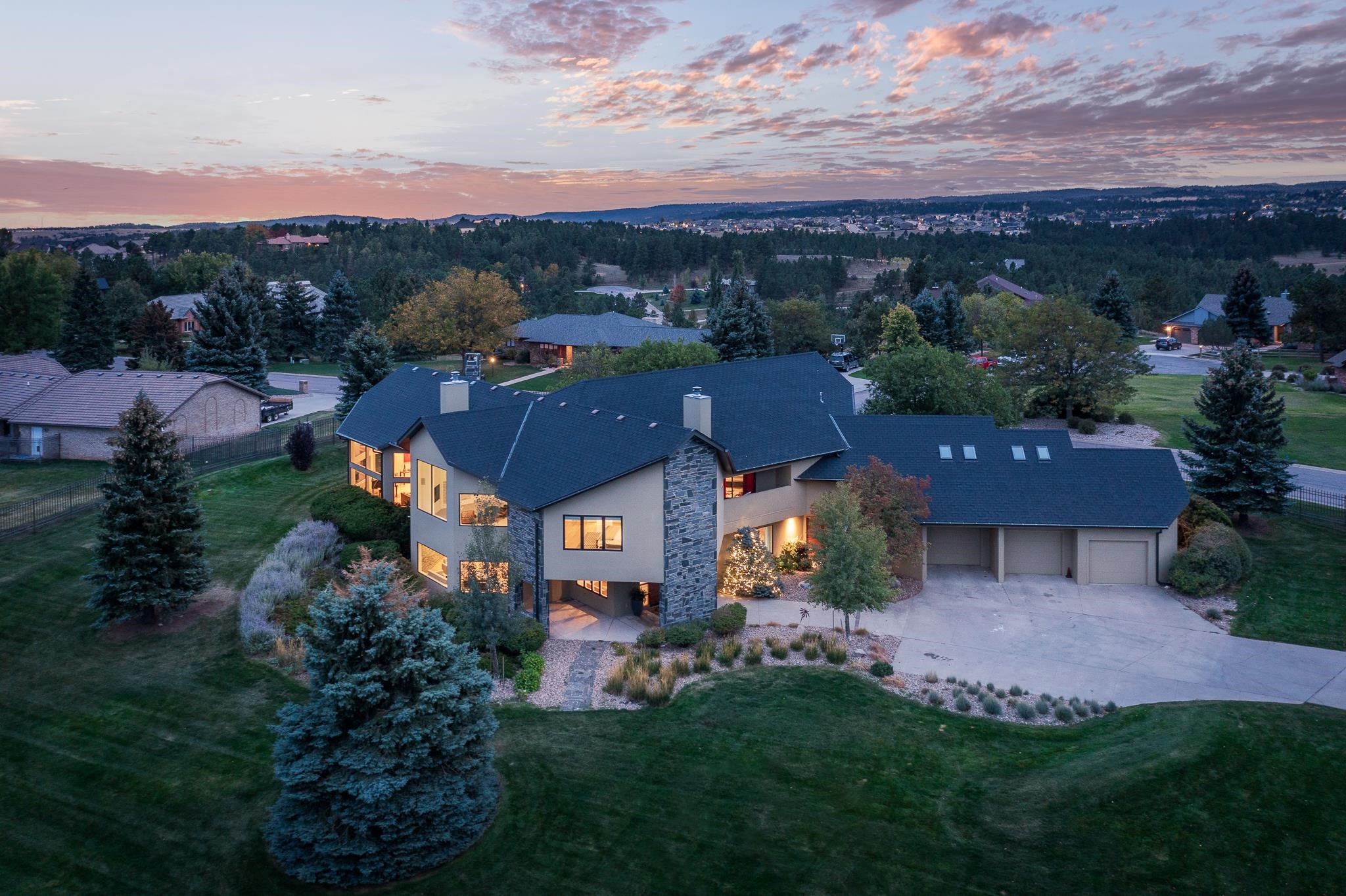 """A Contemporary Masterpiece situated on 1.41 fenced acres within the prestigious Carriage Hills neighborhood offers stunning panoramic views of the Black Hills. The home flows into a luminous, open-concept living, dining, and chef's kitchen with a gas Wolf range, double ovens, Sub Z refrigerator, wine cooler, and oversized kitchen island with quartz countertops. The main level features two grand fireplaces, family, living and dining rooms, an oversized office, a guest bedroom with en-suite bath, and a large laundry and """"drop zone"""" with beautiful built-in cabinetry. The upper level features three large bedrooms, all with private ensuites. The primary bedroom features oversized windows and attached sitting room - perfect for enjoying your morning coffee while gazing at the hills. The spa-inspired bathroom boasts an oversized steam shower, tub, and custom vanity. The additional bedrooms are generously sized and boast covered patios, bringing your guests a resort-like feel."""