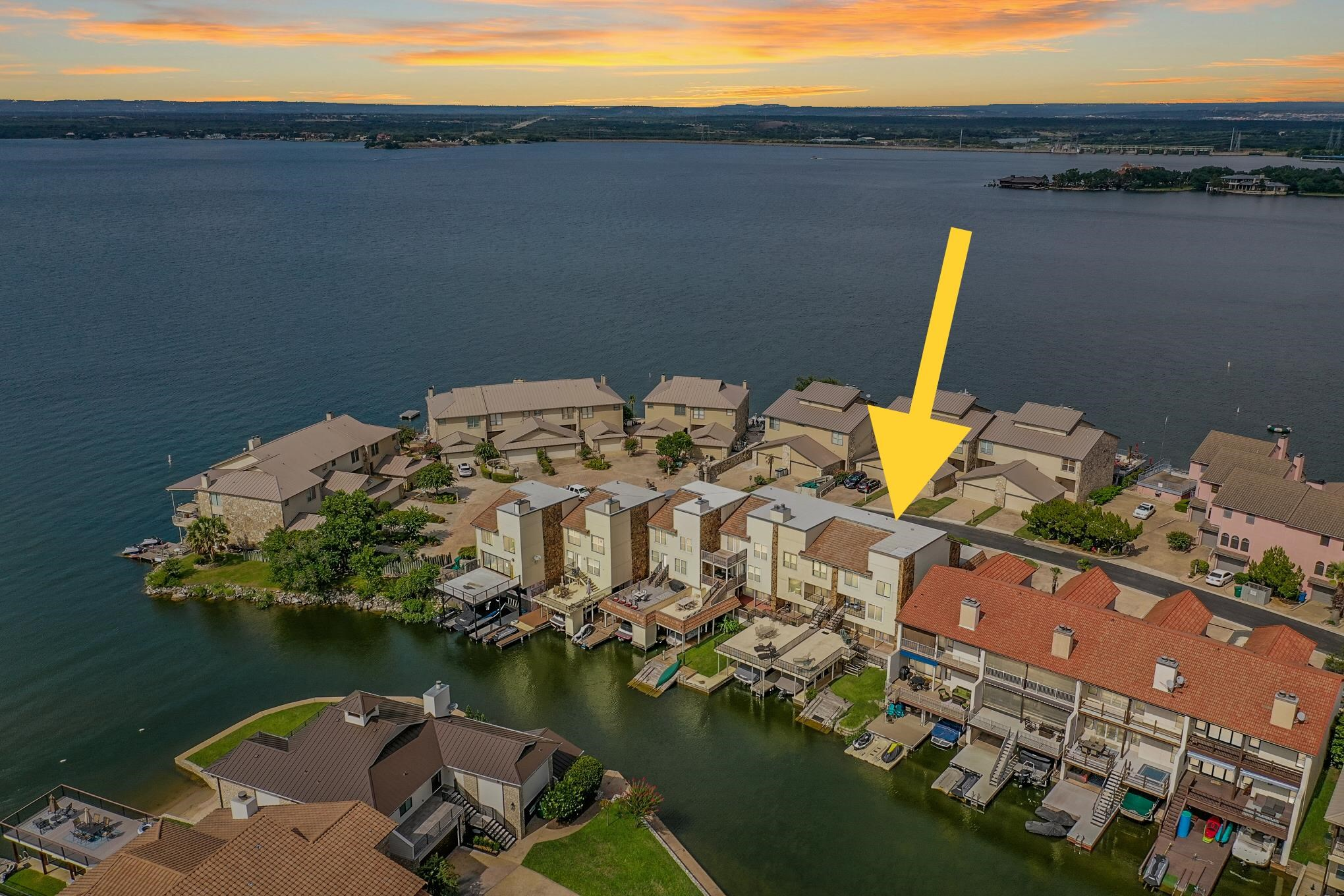 Lake LBJ Luxury Townhome:  Picture perfect waterfront townhome centrally located in the heart of Horseshoe Bay, is ideal as a full-time residence, a weekender, or investment property!  The foyer of this meticulously remodeled get-away welcomes you home with up-to-date finishes, open water views, and a floor plan ideal for family and guests.  Step up to the main living area where the great room presents glorious views to the cove and beyond to big, open water.  The efficient kitchen's pearl white cabinets, smoke colored counters, and gleaming stainless appliances make entertaining a breeze.  Unwind inside or step out to the deck to relax after a hard day on the lake or links. Three quiet bedroom suites are tucked one floor above where the master brags water views and an en-suite bath with a large walk-in shower.  Two additional guest rooms each boast en-suite baths, making it easy to accommodate family & friends. At lake level, the bonus room offers countless possibilities with a full bath and cedar-lined sauna.  Step outside to your covered boathouse and jet ski ramp where many of the Resort's amenities are a quick ride across the bay.  Spend summer afternoons fishing or sunbathing from your deck, take a dip in the water, or embark upon a day on the lake.  As evening falls, enjoy your favorite cocktail as you count the stars and watch the moon glimmer over the quiet lake.