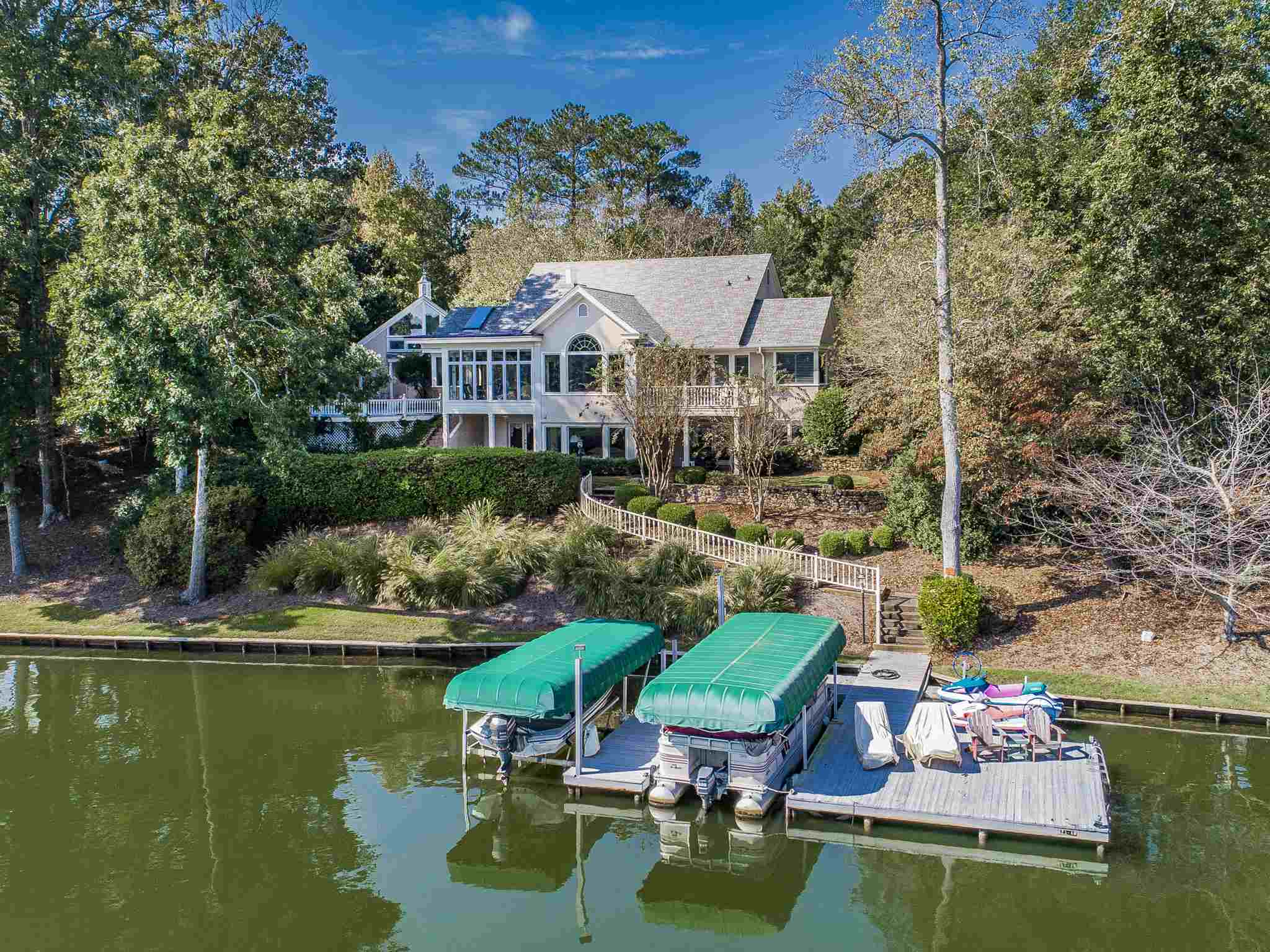 Come home to this charming lakefront home on the shores of Lake Oconee. Views of the lake are seen from every room of this 4 bedroom home. The flow through the Main Level begins in the lovely foyer inside the front door and winds through the dining room, skylit kitchen, breakfast room, and a great room with a fireplace. The Main Level includes a large, private master suite which includes a bathroom with marble counter tops, double closets, and a jetted tub. Outside the breakfast room door is a spacious patio which offers a panoramic view of Lake Oconee as well as room for cooking and dining. The Terrace Level features two large Master Suites on either side of great room featuring another fireplace and a wet bar. Above the garage is a fully featured efficiency apartment for family or guests. Lake activities are just steps away with a max dock with two boat lifts and two jet ski lifts. Golf membership available.