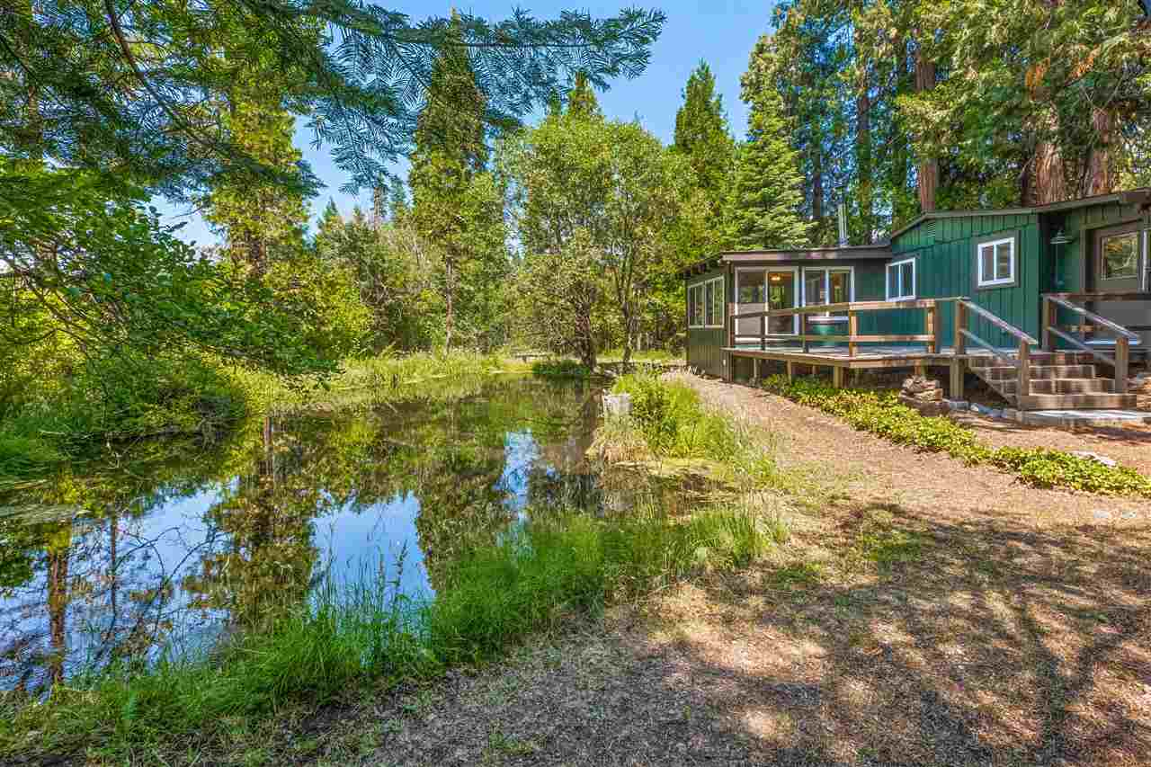 Unbeatable location! Absolutely stunning setting! Rare opportunity to purchase a home 2 minutes from downtown Mt. Shasta with creek frontage and pond. This 1476 sf. 3 bed, 2 bath charming cabin is situated on a 1.3 acre parcel that has approximately 200 ft of Spring Creek running on the southside of the house as well a pond on the northeast side of the house. There is a large 2 car detached garage and a separate workshop on the property. This gem features a big living room, rock hearth fireplace, large picture windows, Mexican tile in the kitchen and dining room, and a amazing sunroom overlooking the pond. The property also sports a peak a boo view of Mt. Shasta through the fir, pine, and cedar trees. The house is located in the middle of an abundance of outdoor activities and has a very secluded feeling.