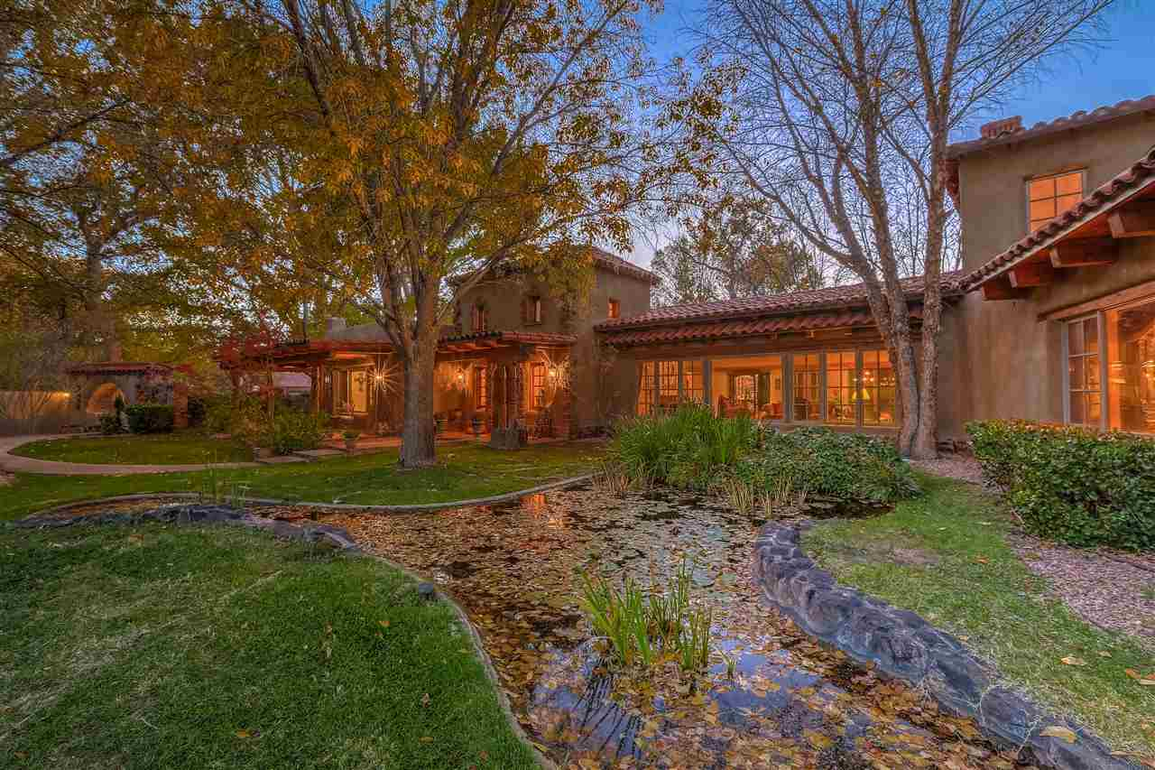 Breathtaking! Coveted Eakes Rd/Los Poblanos area of Los Ranchos. Charming, elegant, 4-5 bedroom adobe home designed by John Calvin. Situated on 2.4acre landscaped estate lot backing to bosque and trails of the Rio Grande, this home and guest house provide the ultimate in privacy and verdant beauty of the North Valley. A beautiful brick barrel vaulted entryway welcomes you to this warm and inviting home. Flagstone floors throughout living areas, intricately carved beams and doors add to the Moorish/New Mexican design of the home. Updated kitchen with granite and high end appliances. Master bath with marble, granite and travertine evoke Roman bath. Portals, fireplaces, water features, gardens combine styles of traditional New Mexico and classic Spain. Refreshing pool, spa; adjacent guesthouse/cabana!