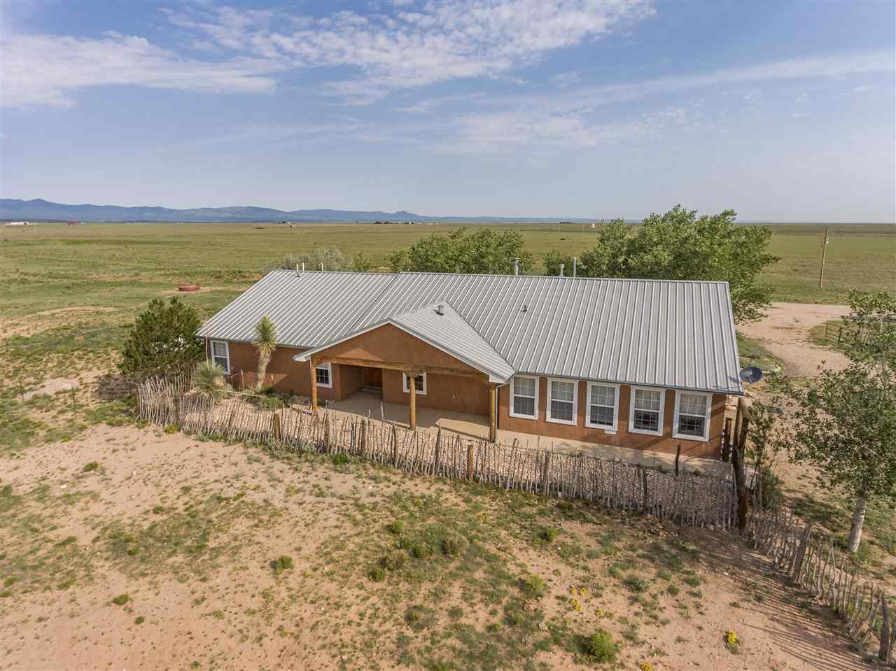 This central New Mexico scenic equine & cattle ranch is just east of Mountainair and sits on 296 acres of blue gramma grass. The property is fenced and cross fenced, a 64 x 80 horse barn, 30 x 60 metal shop barn, 25 x 50 hay storage shed, and a 150 x 300 outdoor riding arena. There are a multitude of pens, a cattle loading chute, electronic scales and a 384 sf bunk house or guest house. The home is 2156 sf of heated space with 4 bedrooms and 3 baths, garage is 578 sf. The western themed home has many artistic features and boast cowboy country charm throughout. The covered porch faces the northwestern mountains for spectacular mountain views and amazing sunsets. If your dream is to own a horse property where you can ride and run a few head of cattle year round, this is it, look no further. Albuquerque and Santa Fe NM are both within easy driving distance.