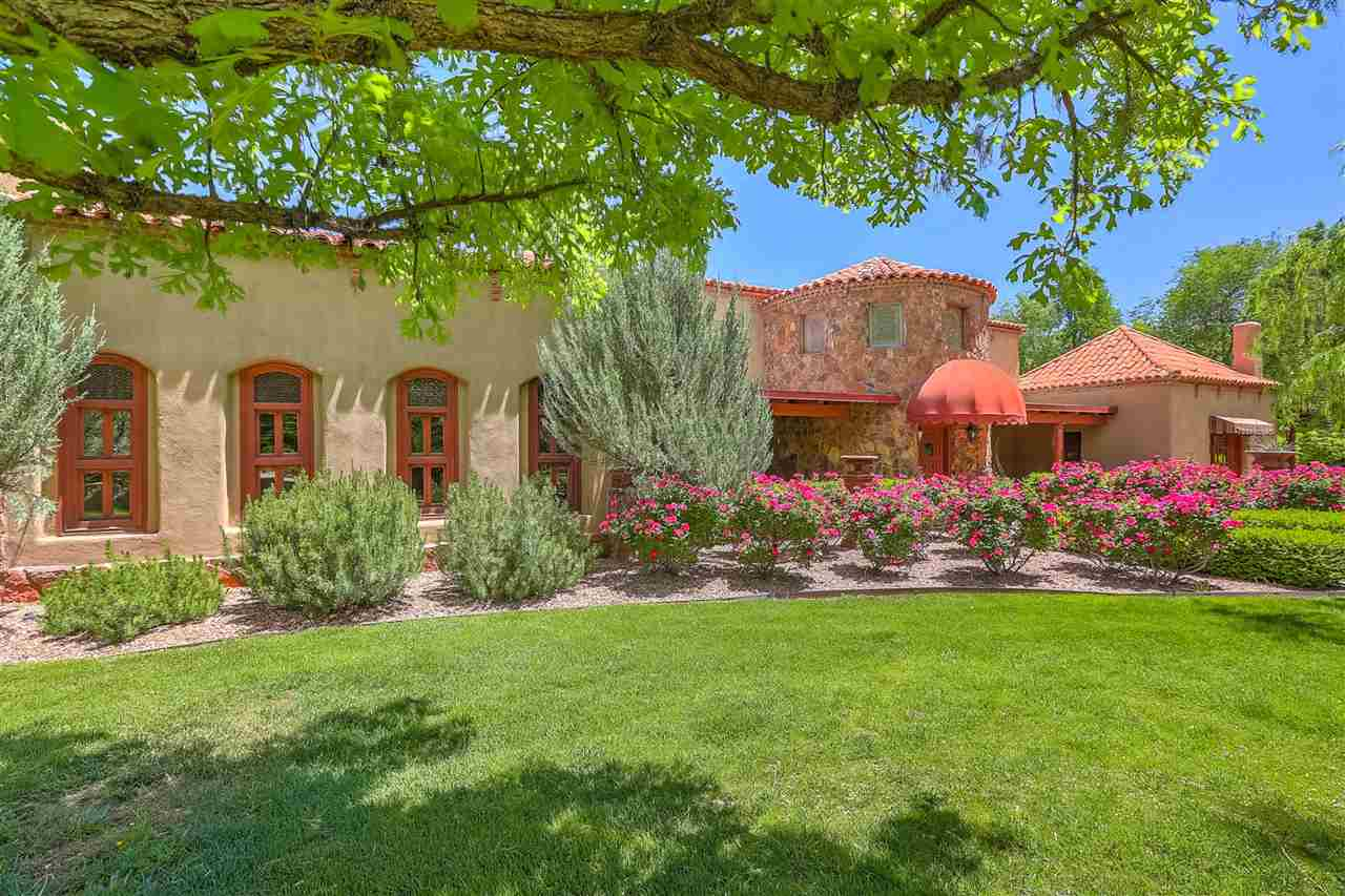A Los Poblanos exquisite lifestyle estate brilliantly designed by John Calvin and completely updated by the current owners. Arrive in style through the impressive gated entrance graced by lush landscape, waterfall and koi pond. 5.84 fully fenced acres featuring producing vineyard, livestock pastures, 5040 sq. ft. main home, 2340 sq. ft.  full casita with office, tasting room and wine cellar, and separate livestock quarters. Artfully crafted bell tower gate and colorful rose-lined path guide guests to the main home entry revealing the great room, graced with cathedral ceilings and multiple sets of doors opening onto the back patio and gardens surrounding the magnificent outdoor pool entertaining area.  Extensive windows throughout the home provide tremendous natural lighting and spectacular views of the estate gardens. Remodeled kitchen off the dining wing is appointed with top-of-the-line appliances. The massive kitchen island includes storage and easily seats four. Master bedroom enjoys spa-like bathroom and oversized separate closets. Three additional bedroom en-suites are included in main home. Oversized detached guest house is carefully and artfully crafted as the main home, and includes open floorplan great room, full kitchen, single bedroom and one and one-half bathrooms.  Adjacent tasting room with office and barrel ceiling complete the casita. Easy access to downtown, Albuquerque International Airport via I-25, I-40 from  southern end location of the North Valley.