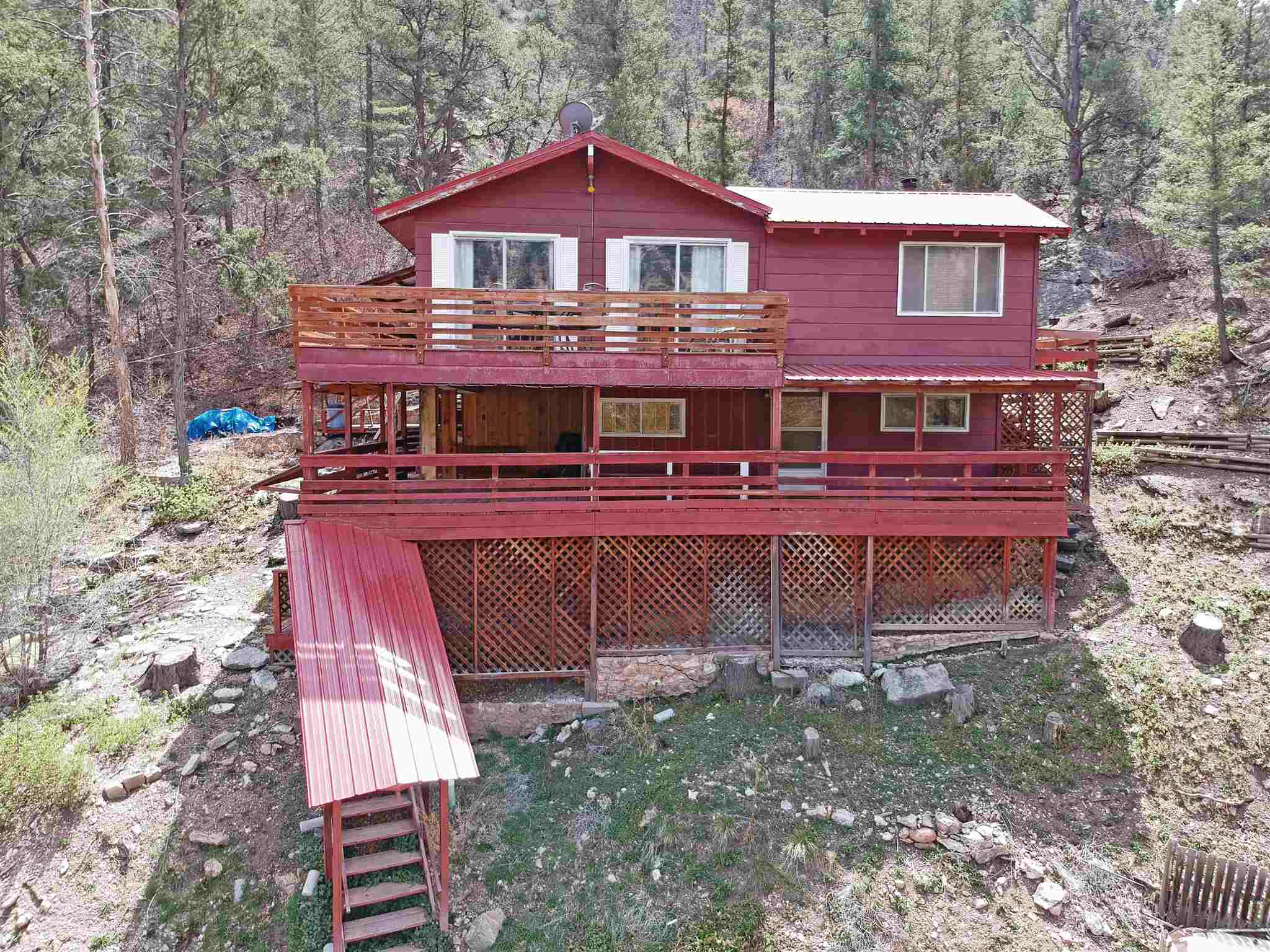 Do you ever wonder what makes the Jemez so appealing? Well step onto one of these wrap-around decks at this beautiful home and you will know instantly! Tucked away in a quiet area near Jemez Springs is this great getaway, within walking distance to the Jemez River and many other outdoor adventures. The living areas are warm and inviting, with a vaulted wooden ceiling with exposed beams, a lovely fireplace, wood burning stove and sliding glass doors that lead out onto one of the two decks with breathtaking views of Virgin Mesa. Cozy kitchen and open concept dining area. Two bedrooms on the main floor and two more downstairs in the finished walk out basement, with a bathroom on each floor. Don't wait on this one, schedule your showing today.