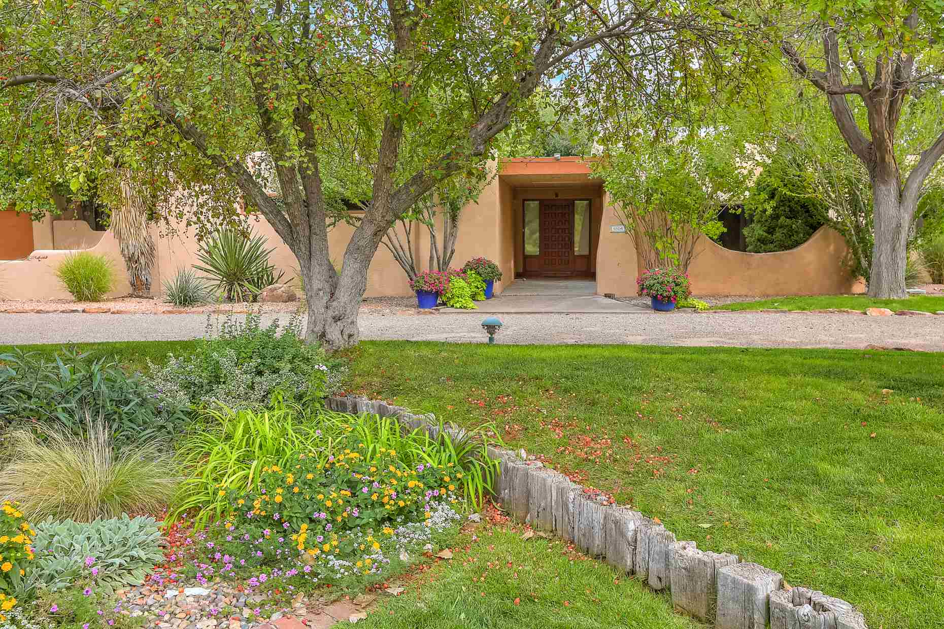 Rare find in this special pueblo revival home in the coveted El Caballero Ranchitos neighborhood in the verdant North Valley. Lush landscaping and a tree-lined acreage lead into a gracious courtyard and gallery entry. Options for living and entertaining include a formal living room with fireplace, dining room and a splendid large family room with fireplace, bookcases and a private patio. Gather around the center island in the updated kitchen which features granite and SS appliances. The master suite has a closet to die for! Adjacent to the master is a very large office/studio with a separate entrance. There is lots of space in the four additional bedrooms. A gathering area for meals or relaxation and conversation is the light center atrium. Sweet guest house with BR, BTH, FP & garage.