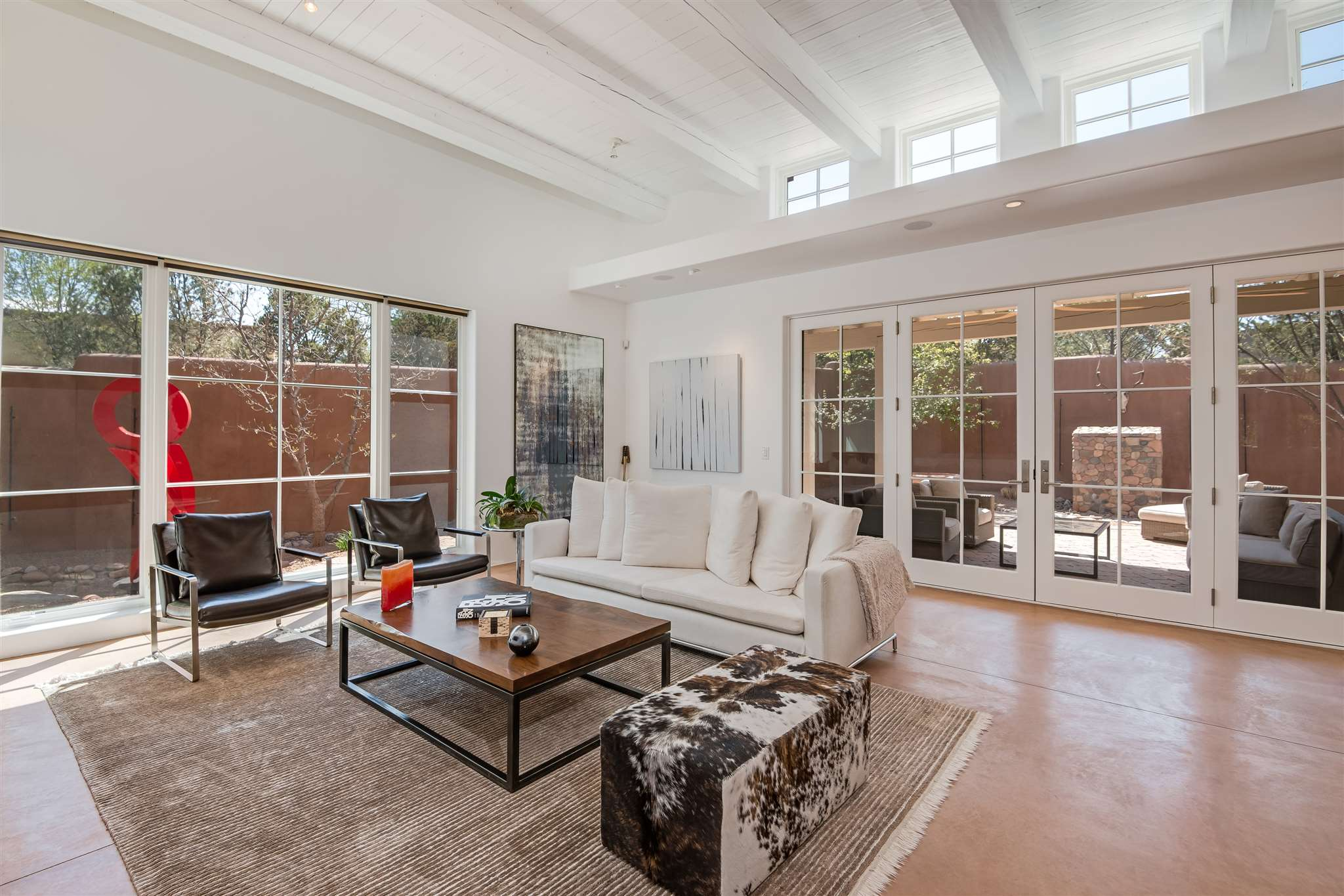 Rarely available and greatly coveted is this single level (no steps!), soft contemporary, energy efficient, 2 BR, 3BA home in the Historic Eastside within walking distance to Canyon Road and the Plaza. Built in 2011 by Doug McDowell, and located in the small, private compound of Las Placitas, this gorgeous 2,359 square foot residence offers an open floor plan with high beamed ceilings in the great room, a gourmet kitchen, ample wall space for your art collection, and wonderful natural light. The two bedrooms are well separated for privacy and enjoy en-suite bathrooms. The home also offers a powder room, oversized laundry room, and a 2-car garage.  Step out through the French doors onto an inviting portal nestled in a high walled garden with rock spillway fountain and outdoor fireplace perfect for entertaining.  Other features include concrete floors, custom woodwork, an irrigation system, and solid masonry construction (ICF).  This residence is also LEED Gold Certified and includes a state-of-the-art efficiency evaporative cooling system, air filtration system, photovoltaic electric power, in-floor radiant heat, a solar domestic hot water heater, and a home water catchment system.