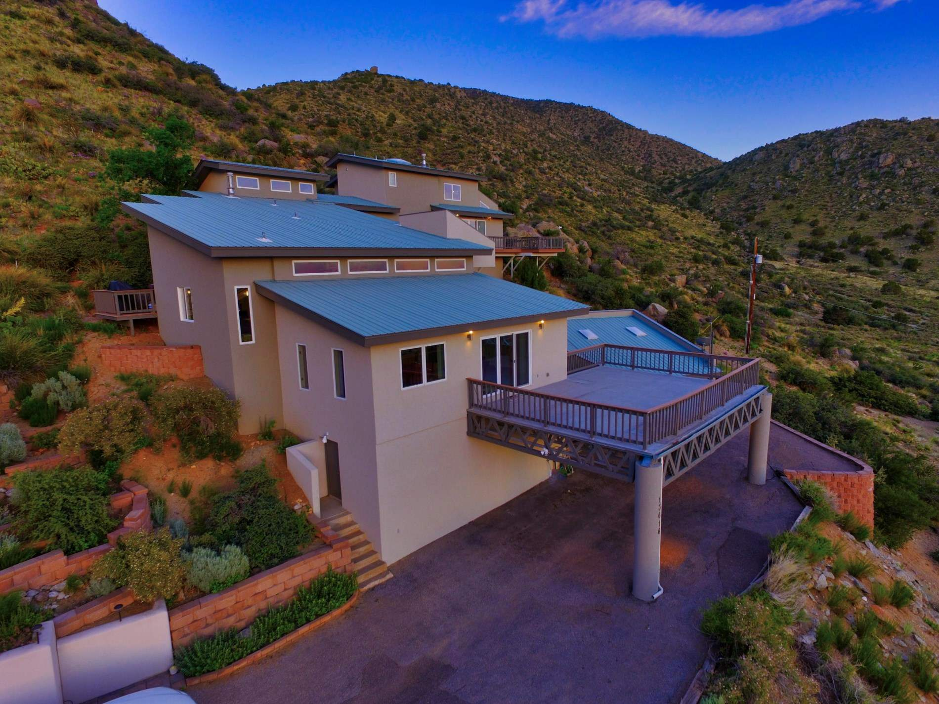 Contemporary living, modern elegance, & tranquility await you high up on the hill! An artistic and open floorplan. Offering unobstructed views as far as the eye can see! Sunset views of Mount Taylor adorn the evening sky. Surrounded by open space to the east & south and direct access to walking trails.. This unique custom split level home is a certified wildlife habitat and frequently enjoys visits from a wide variety of animals. The complete remodel brings modern color and flair to this amazing dream home!  Designed by a local architect to be his own personal domicile, great care was taken to capture the best views & take maximum advantage of the solar gains. Enjoy the magnificent custom etched glass mountain landscape that accents the living area. There are 4 separate decks surrounding the home to maximize outdoor living space. The open floor plan makes this home ideal for entertaining. There are 2 REFRIGERATED AIR units! The master bedroom is located on the upper level and is separate from the other bedrooms. The master bath boasts teakwood sinks and tub. Grab your favorite drink and your cuddle buddy and enjoy the private pati  The open floor plan makes this home ideal for entertaining. There are 2 REFRIGERATED AIR units! The master bedroom is located on the upper level and is separate from the other bedrooms. The master bath boasts teakwood sinks and tub. Grab your favorite drink and your cuddle buddy and enjoy the private patio space! The views are unbeatable! Cheers!
