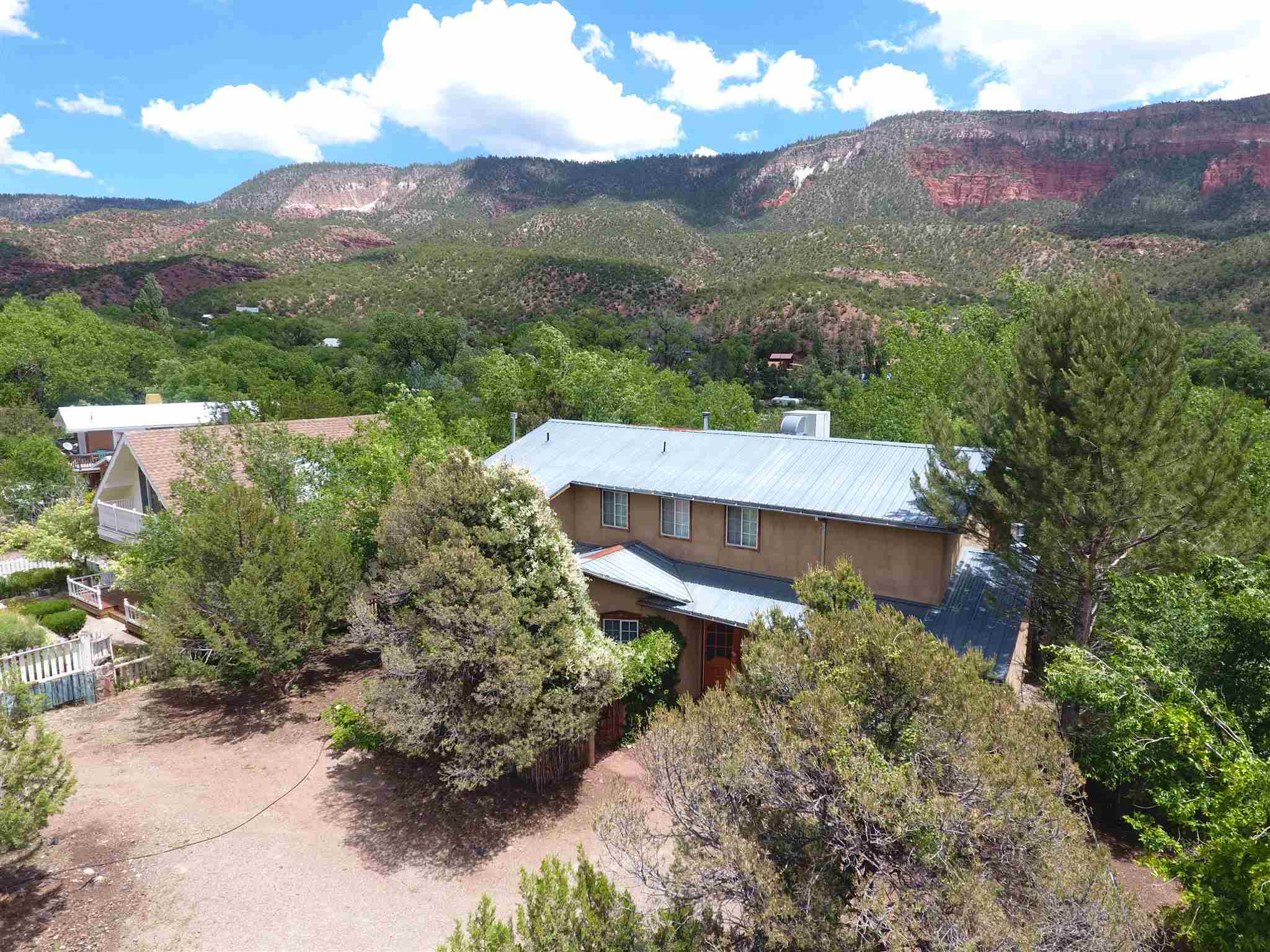 An AMAZING blend of heavenly Jemez Highlights! Perched just above the Jemez River, the fabulous home was located, designed and built to take it ALL in! Beautifully maintained and well built! Living Area and 4 generous bedrooms, 1 on main level & 3 on 2nd...EACH & EVERY ONE with sliders to the AMAZING double decker screened porches sitting right over the river!! Imagine those summer nights drifting off to that wonderful sound!! Absolutely stunning VIEWS all around. Attached 2 car garage now doubles as a game room. Located right in the Village, for easy walk to everything really, post office, library, restaurants. . Used for several years as a successful VRBO! All the beautiful furnishings remain if you want them. City water & sewer so no well or septic to worry with. Bring the fishing gear!