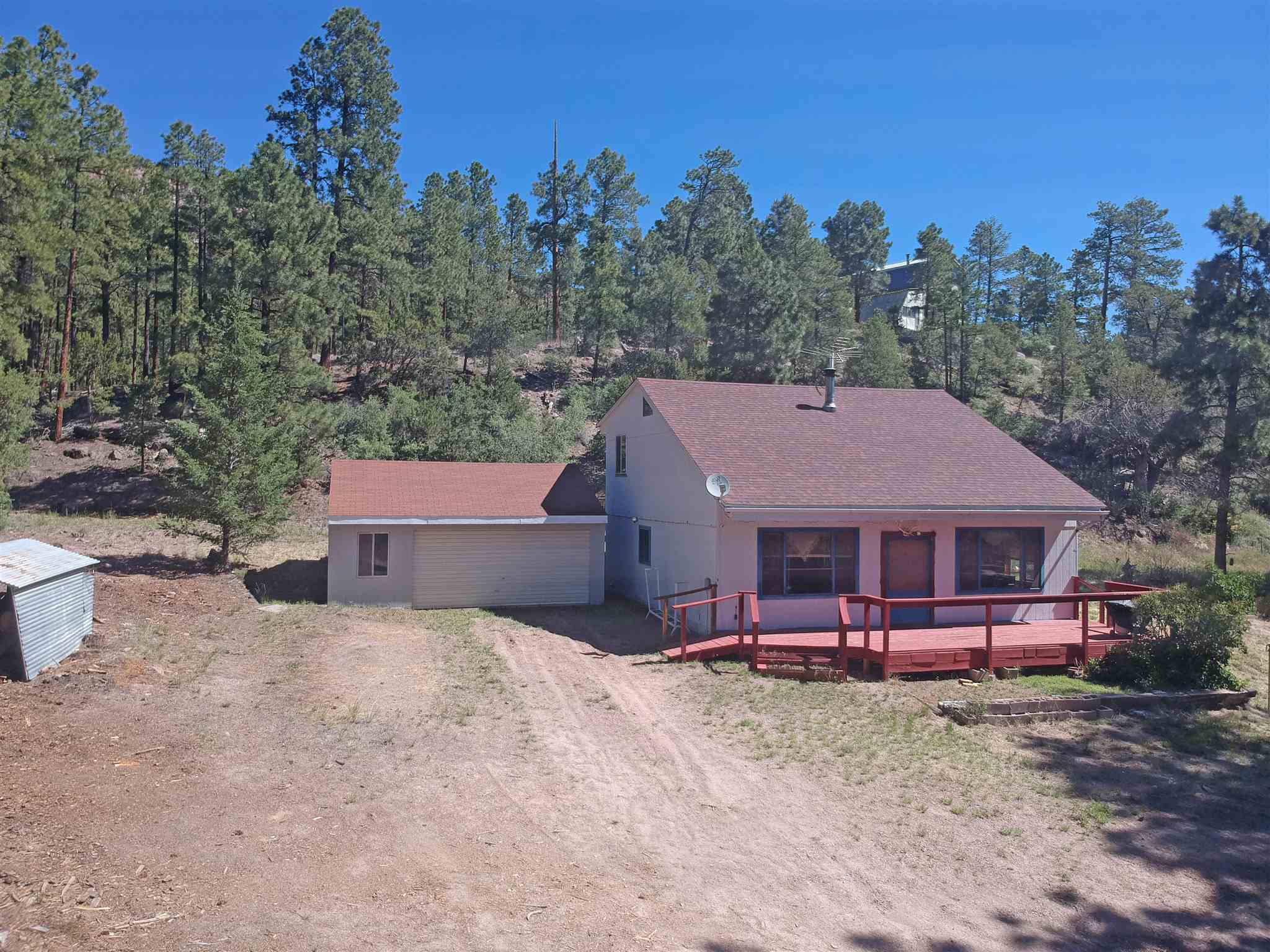 Move up to the Cool Pines subdivision into this home that is ready for you to add in some of your own creative finishing touches. This three-bedroom, two full bath 1,436 sq foot home sits on a 1-acre lot with a garage and plenty of room to spread out or plant a garden. Open concept living room, dining and kitchen area with a centrally located woodstove to cozy up to in the winter months. The living area has a lovely knotty pine ceiling and  laminate wood flooring that makes you instantly feel at home.  The remainder of the home is ready for you to install the flooring of your choice. This property is loaded with potential, and ready for a buyer to come in and make it their own!