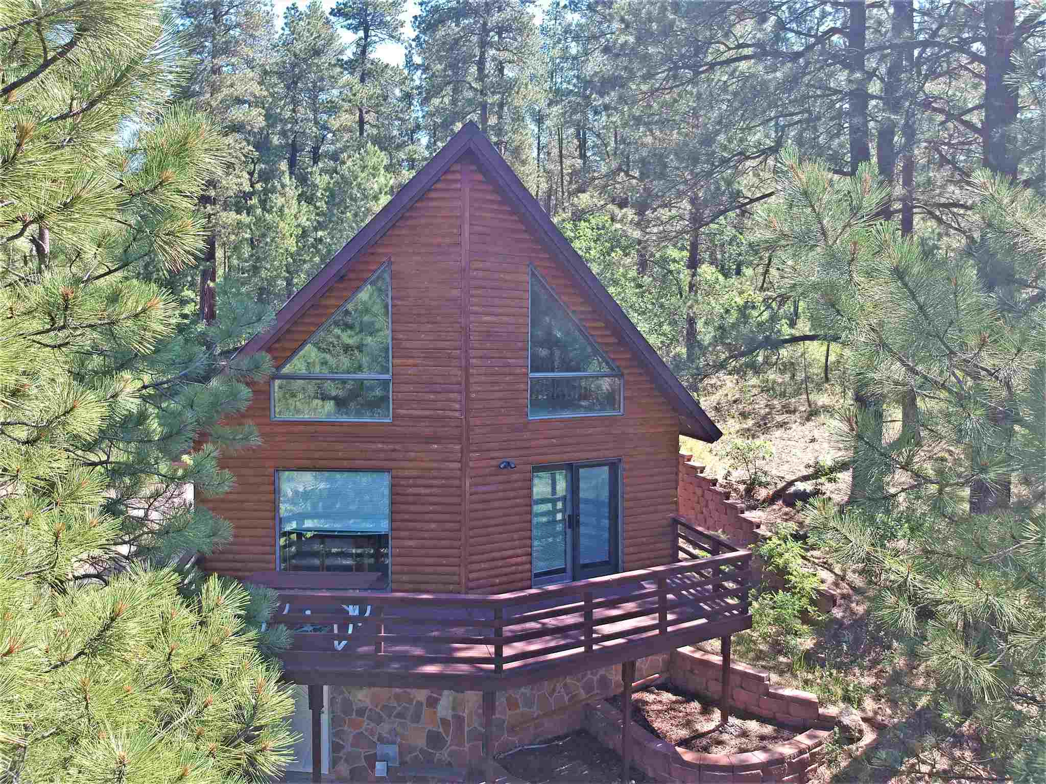 Step out the back yard into the Santa Fe National Forest! A few steps further, you're on the Valles Caldera National Preserve. What an opportunity for a mighty big ''back yard''!! DON'T MISS IT!!! Commute to Los Alamos in 30 minutes or so! Ample room to spread out inside too! 3 fabulous levels to play with! Game room? Library/study? Guest rooms? BEAUTIFUL upper level has a big bedroom, PLUS a LOVELY bonus room with wonderful floor to ceiling windows, really great for almost anything! Main level is 2 good sized bedrooms, full bath and sweet, open kitchen/dining/living opening to a deck that will have you pining for the pines! Lower level is 2 more bedrooms, 3/4 bath and again...BIG space for whatever you need it to be! Beautifully maintained home...move-in ready, All furnishings can stay!!