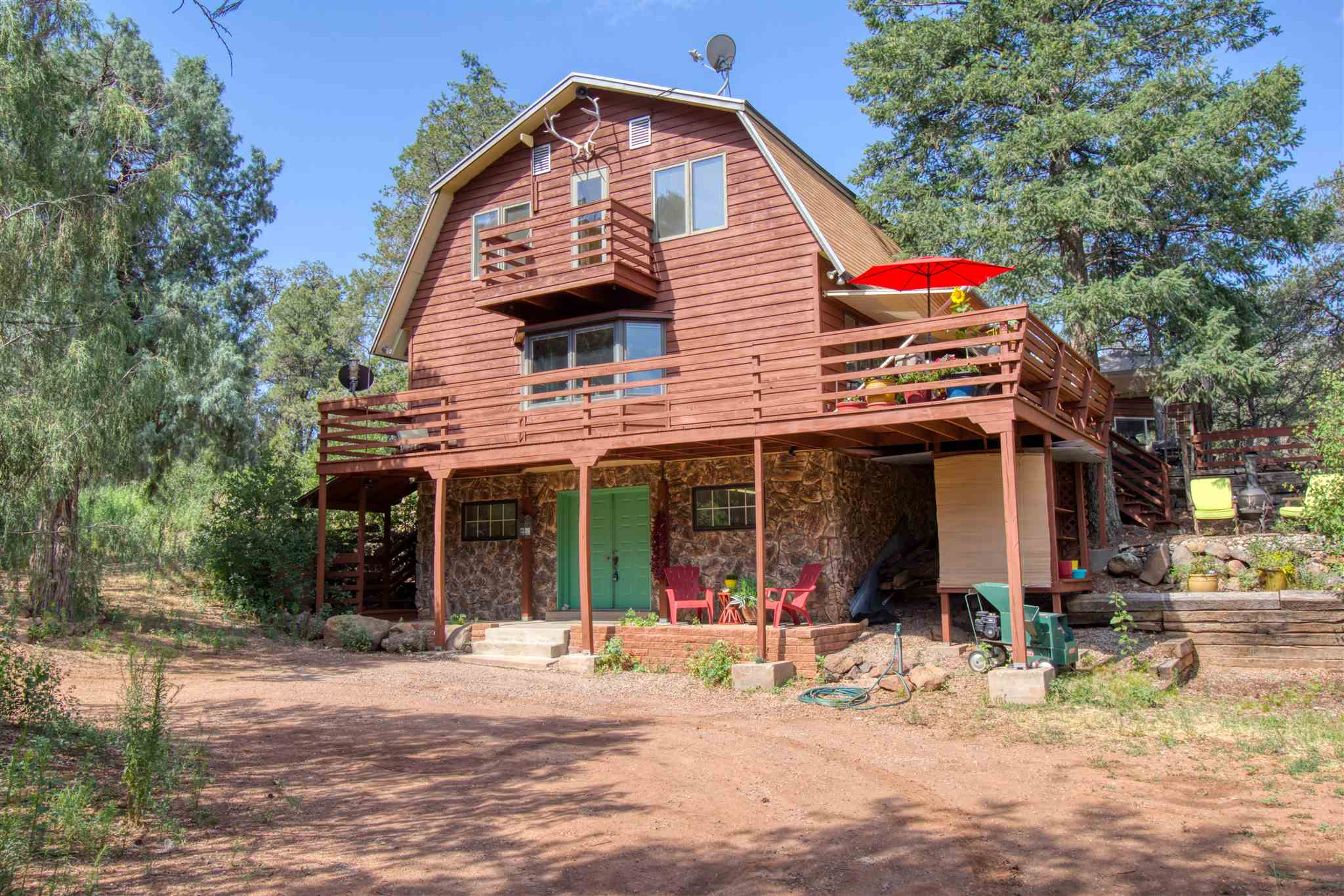 Your mountain oasis is now available!  Surrounded by pine trees and solitude, this well-built Jemez home is sited on over an acre of natural beauty.  The wrap-around deck and covered awning provide you with outdoor living space to enjoy the sounds of wildlife in your natural retreat.  You can further relax in your top-floor master suite, complete with its own fireplace, sitting area, and walk-in closet.  The master bathroom has a walk-in rainfall shower and a double vanity.  Slate floors and tongue-in-groove ceilings complete the high-end look and feel.  A second top-floor bedroom opens onto a balcony with views up the valley.  An additional large bedroom with a walk-in closet and attached bathroom is located on the main floor.  The kitchen, living room, and dining room make up the remainder of the main floor living space, which also opens onto the wrap-around deck.  A spacious laundry room is located past the kitchen.  The ground-level floor contains additional space for your workshop and storing your toys.  There is also space for your larger toys in the detached carport.  The property can be sold with the furniture, so you can start enjoying your mountain living right away.  Come make this mountain oasis yours today!