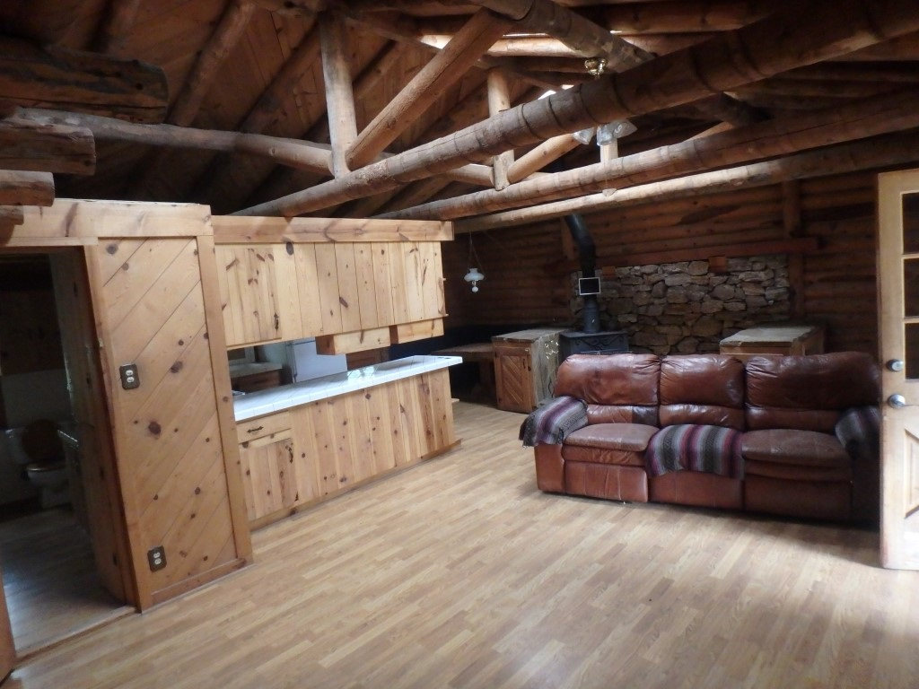 This is a real log home at almost top of the hill in Hidden Valley Estates. It's built with 2 stories heated but access to basement is from ground level while stairs lead to front doors and deep covered deck overlooking the La Cueva Valley. The home is fairly simple, open design with 2 thirds of main floor being mostly log and cedar with a combination great room featuring kitchen, built in dining, wood stove and living area. The master suite has been upgraded to more contemporary finishings and has second bathroom and door to deck. The basement has a large workshop, laundry room and about an 800 square foot family room. There is an out building used at times for animals and at times as a garage. The main floor is approximately 1349 square feet and the lower floor approximately 1000 square feet. Easy to find off Hidden Valley Road.