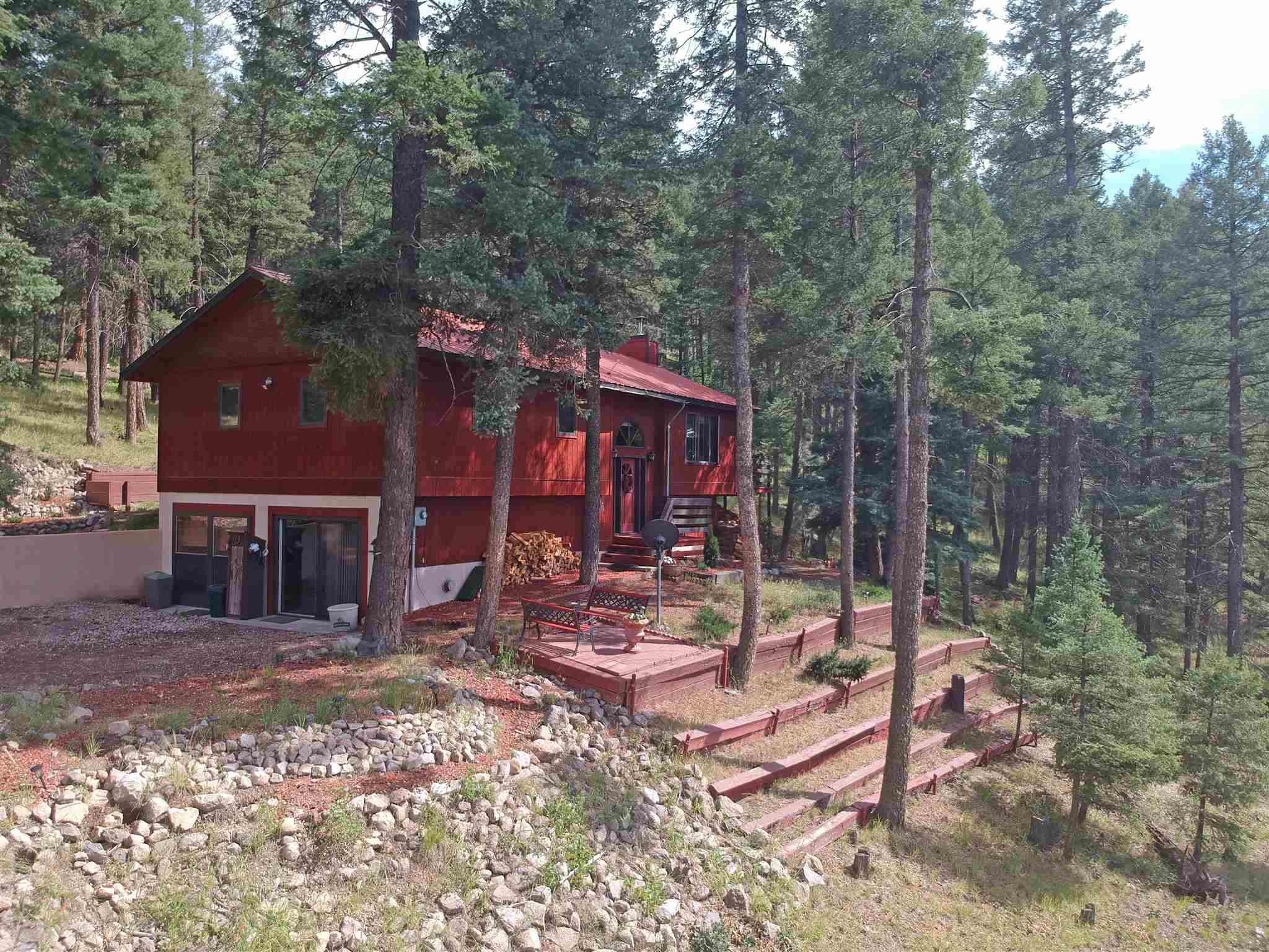 Life is good when you wake up every day to this stunning view AND have the Santa Fe National Forest as your extended backyard! Take it all in on the spacious deck of this well built, sturdy 4-bedroom, 2 bath home with a home office. Open concept living room & kitchen with plenty of counter space & cabinets. The garage has been closed in & made into a rec room, but could easily be converted back if you prefer. Situated on over 2 acres of thinned Ponderosa Pines, within the Sierra los Piños Subdivision, the delightfully landscaped property backs up to Santa Fe Natl. Forest and has an old abandoned logging road leading right into it just waiting for you & your outdoor adventures. Minimal road traffic makes it quiet and peaceful, but yet just a short 30-minute drive into Los Alamos.