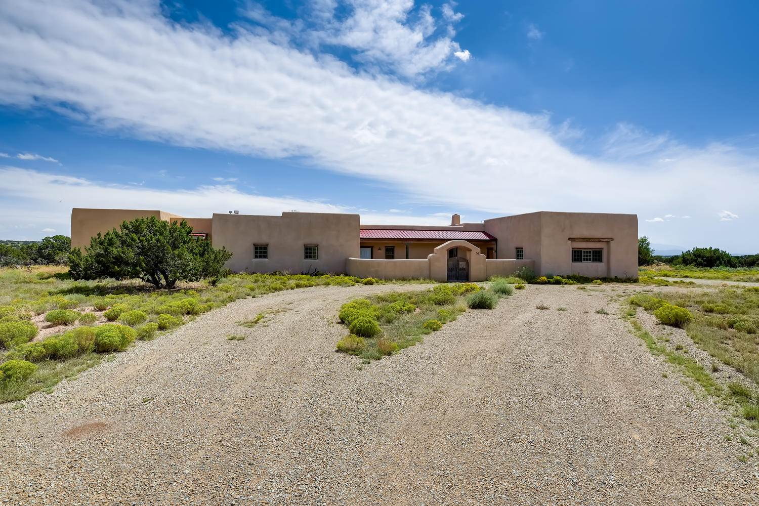 Light, bright, and inviting 3 bedroom/3-bath home on 4.5 acres with Southern views.  This single-level, pueblo-style home offers a 2,082 square feet open-concept floor plan with an attached 2-car garage. Weathered, wooden doors open to an enclosed courtyard, a stone path leading to the cheerful front portal.  A large living space opens before you, bathed in natural light, where the formal dining area, adjoining kitchen, and living room, (with corner kiva fireplace), create the perfect flow for guests. A delicate balance of old world charm, simplicity, and function are achieved in this enchanting home. Large vigas accent the high ceilings, richly textured walls offer warmth and maintain a pleasant interior temperature, while glazed brick floors throughout this authentic adobe home anchor your senses. The master suite with its own kiva fireplace and private outdoor patio offers a quiet refuge from this rugged high desert tapestry. Updated appliances, quartz countertops, rich wood cabinetry, and built-in shelving further enhance the thoughtful design. The energy-efficient adobe construction also features a new 665 square foot studio/office wing with separate entrance. This idyllic setting is the perfect balance of country living, a peaceful work place, and proximity to amenities within a short drive of downtown Santa Fe.
