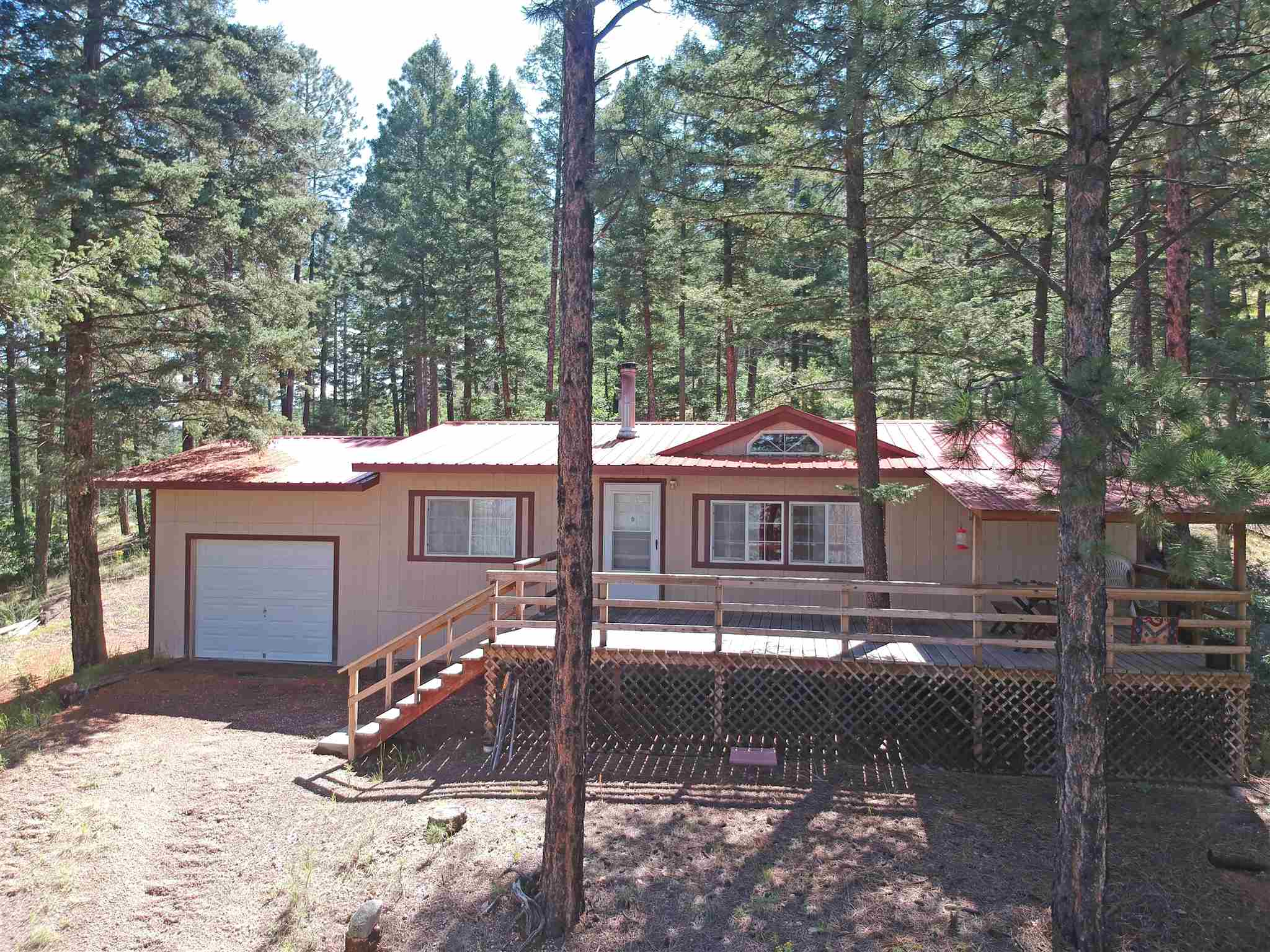 Home away from home or home for good; you found the one! You will love the peace and quiet and beautiful views. Perfect hideaway for outdoor lovers, nature lovers, peace and quiet lovers! Unbelievable view and privacy; mountains, wildlife, hikes, Jemez Falls, winter fun, summer fun, relaxation at it's very best and right in your back yard. Very well maintained manufactured home with a gorgeous deck which has panoramic views spanning down the valley to Redondo Peak. Driveway has two entrances. Single car garage. Furnishings stay with acceptable offer. Very easy 30 minute commute into Los Alamos. Will consider exchange for Albuquerque area home or Jemez Springs area land.