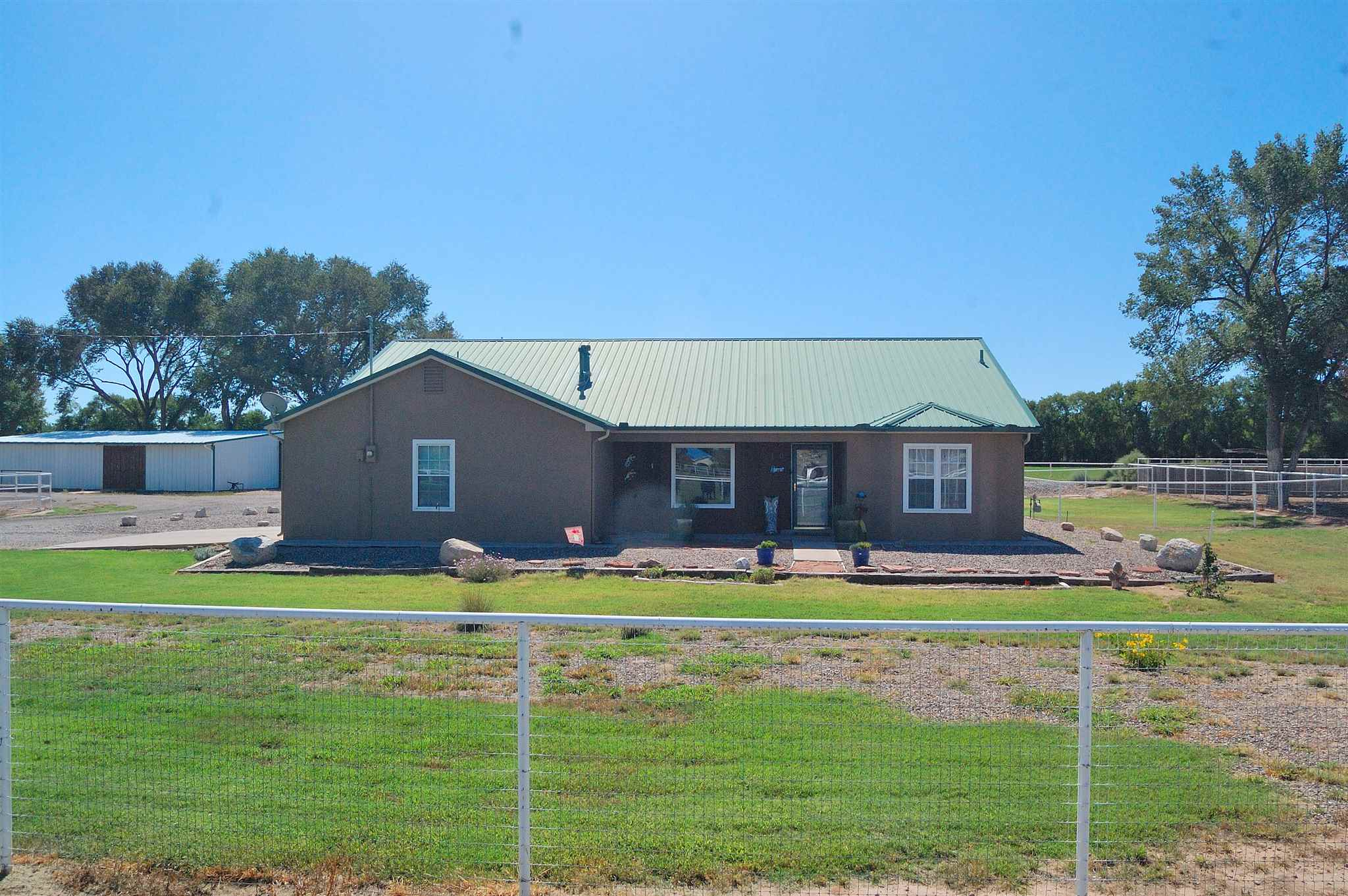 Country Life! Looking for a great home on a quiet country road w/ complete equestrian facilities? Consider this 1800+ sq ft home on 1.7 acres. 3 bedrooms, 2 baths to include a Jack & Jill for the kids. Open floor plan, refrigerated AC, new flooring, metal roof, fully landscaped and move in ready. The back yard is cross fenced with a covered patio and lawn area. Enjoy family time over looking the neighboring alfalfa fields lined with mature cottonwoods. The entire property is pipe fenced, 5 ft with wire, there's a 40 x 60 metal barn with 4 interior stalls, cedar lined tack room, wash bay, hay storage, water and power. Several dbl gates for easy trailer access. The 8000+ sq ft arena is fenced w/ two 12 x 12 stalls, & 2 additional outside pens. Call today for your personal viewing.