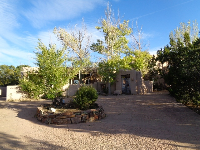 """Gated 5 bed, 3.5 home! This home has 8 fireplaces, a large living room with high ceilings, and also has an attached guest room!Minutes from the Plaza. Traditional Santa Fe features include 8 fireplaces, antique doors, vigas, beams, Saltillo tile floors. The large living room boasts high ceilings, a large fireplace & a wet bar. The professional kitchen is designed with a formal dining room. Master suite, located on the upper level, has 360' views, sitting area & a large bath with tumbled marble. The house features a self-contained, attached guest house perfect for guests. """"The subject is in an online real estate auction.   All offers must be submitted through the auction website Auction.com. All buyer agents must register as the buyer's agent before submitting offers."""