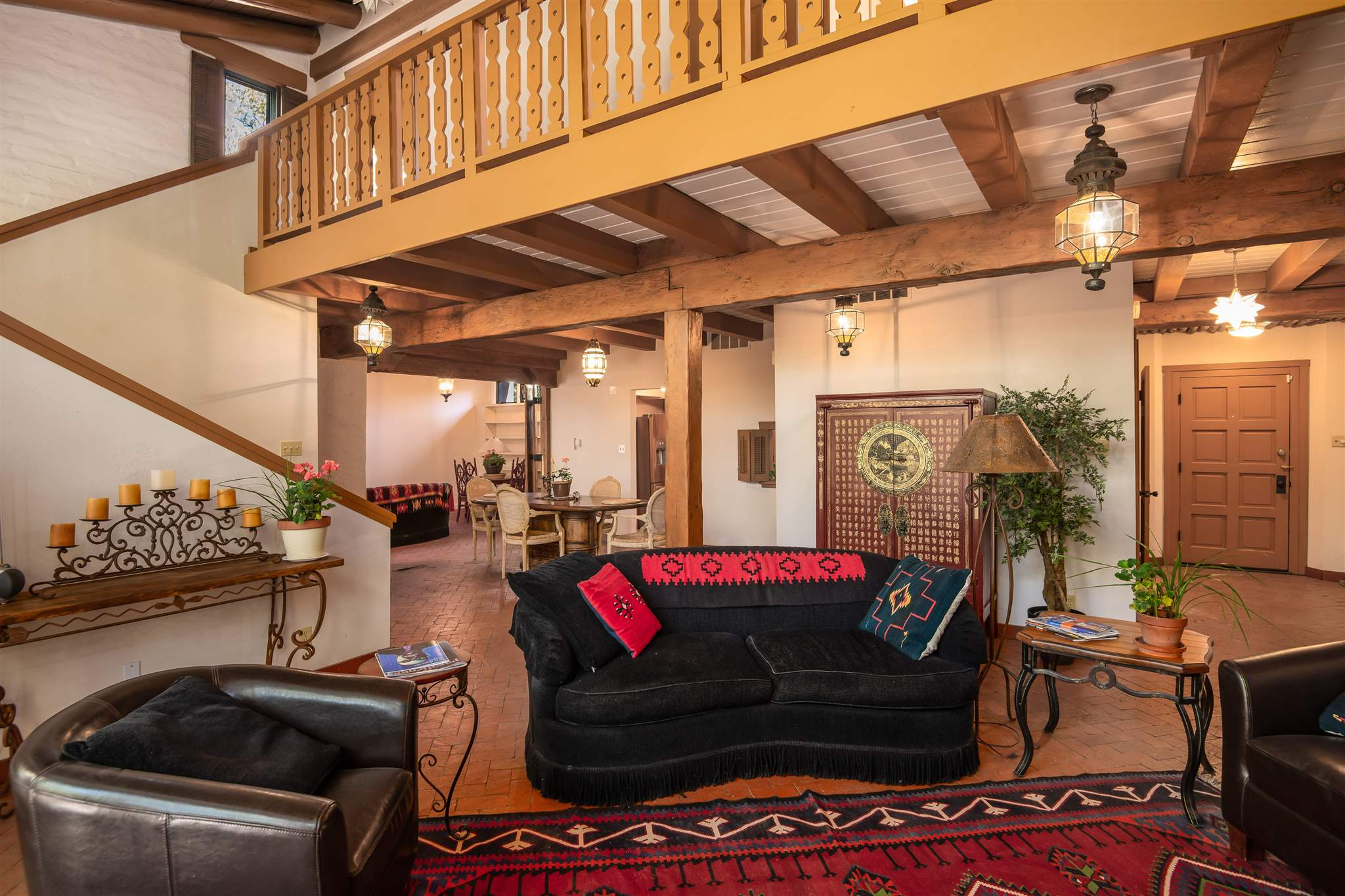 Elegant, private condo now available in La Patria compound, designed by John Midyette and is walking distance to Santa Fe plaza, shops and restaurants. The ambiance of the main level is detailed in Santa Fe Style with interior white-washed adobe brick walls, a kiva fireplace, brick floors and high ceilings with wooden beams. Special to this unit is a large, bonus family room, studio or office.  There's also a full dining room, and powder room on the main level, in addition to an inviting kitchen.  The two-story residence provides privacy for the 2 bedrooms suites upstairs. Enjoy 2,646 square feet of living space, a laundry room with storage with central heat and refrigerated air conditioning and a direct entry two-car garage. Enter through a walled and gated entry courtyard and relax in a shady rear portal with landscaped courtyard adjacent to open space.