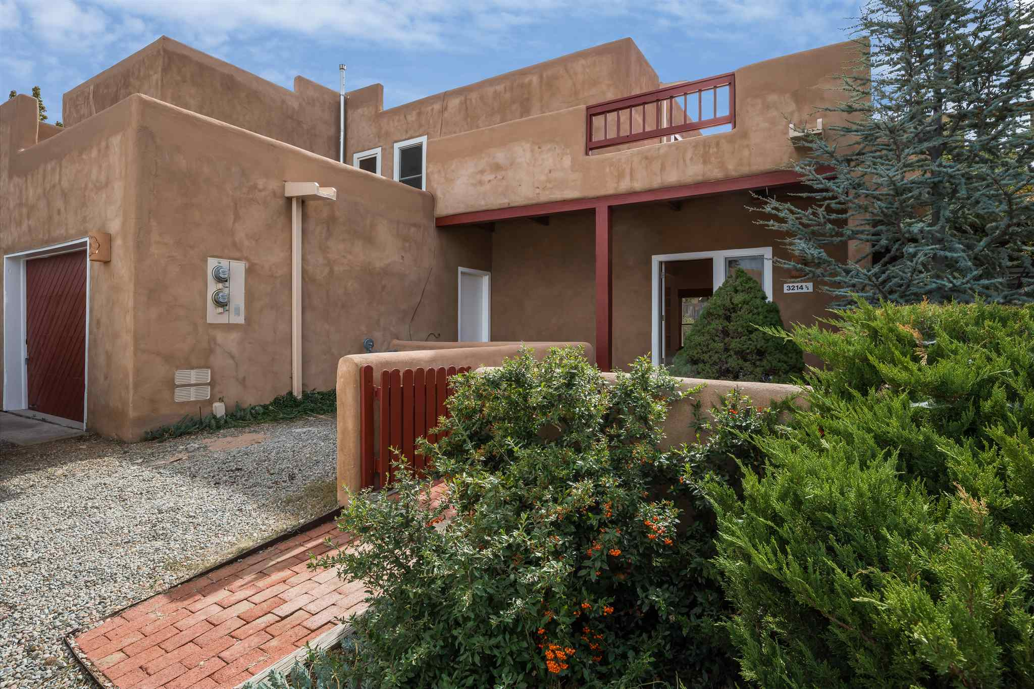 Step into this lovely townhome, with plenty of natural light, quintessential Santa Fe brick floors, and an upstairs deck with views of the Sangre De Cristo and Jemez mountains.  Welcome to Las Quintas!  Centrally located, this home is close to the Genoveva Chavez Community Center, shopping, and nature trails.   A recently remodeled kitchen with a pantry and new appliances looks over an open dining area and living room with a wood burning fireplace and built-in shelves.  There is also a powder room and laundry room on the main level.  Upstairs there are two bedrooms, one full bath, more built-in shelving, and access to the rooftop deck, perfect for stargazing.  Both baths have been recently updated with tile countertops and new fixtures.   An attached, finished garage leads to a welcoming front courtyard and covered entry to the home.  The backyard is fully enclosed by a coyote fence and features a flagstone patio and ample space for gardening.