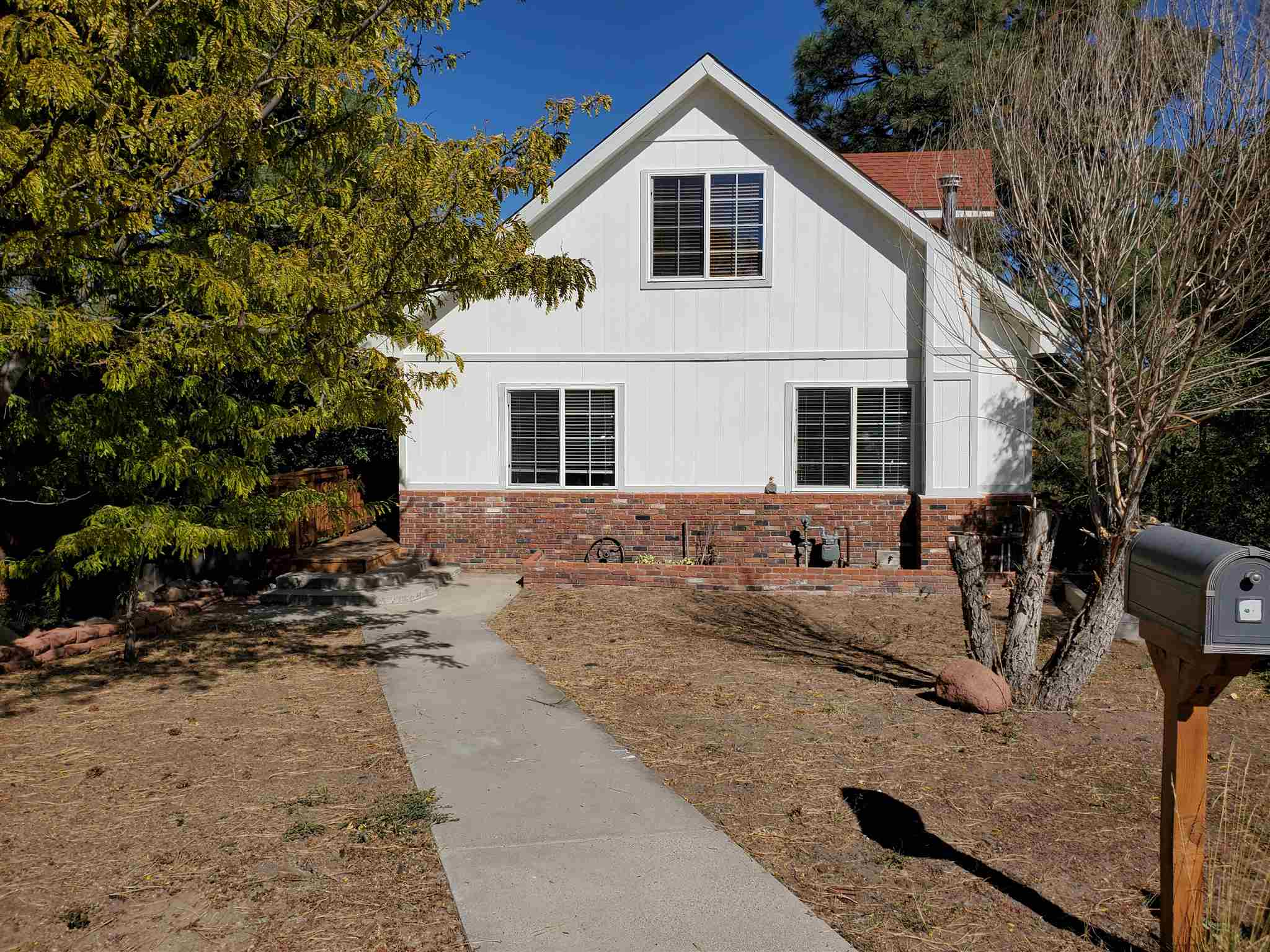 This beautiful multi-story home with a finished walk-out basement is perched at the top of a hill on a cute cul-de-sac, surrounded by tall ponderosa pines with views looking toward the Sangre De Cristo Mountains. You'll walk into the home on the main floor where you'll see beautiful maple hardwood flooring throughout the open concept living, dining and kitchen areas. There are tons of windows for natural sunlight, and sliding glass doors walking out to one of the two large decks at this home, which offer additional outdoor living and entertaining spaces. The kitchen has been beautifully remodeled with granite tile counter tops, stainless steel appliances and maple cabinets.  This floor also has 2 bedrooms and a remodeled ¾ bath. Upstairs is a cozy loft, master bedroom and a lovely remodeled full bath. The basement has brick flooring and a large wood burning stove, one bedroom, full bathroom, laundry/utility room and lots of storage.  This home has been very well maintained and upgraded throughout, and is ready for you to move right in.  A detached 2 car garage faces Alamo Road and has off-street parking for vehicles or a camper.