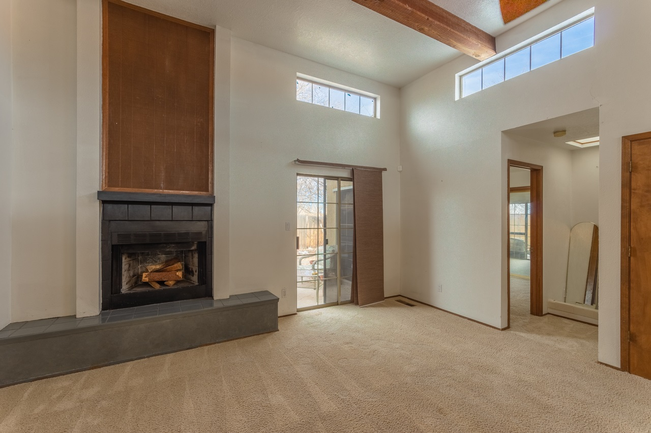 Come take a look at this 2-3 bedroom 2 ¾  bath home in a convenient Santa Fe location! This home could be a 2 bedroom with separate studio or in-law quarters.  High ceilings with wood beams & fireplace along with an open floor plan provide for modern living!  There is a small shed out back for your tools and storage.
