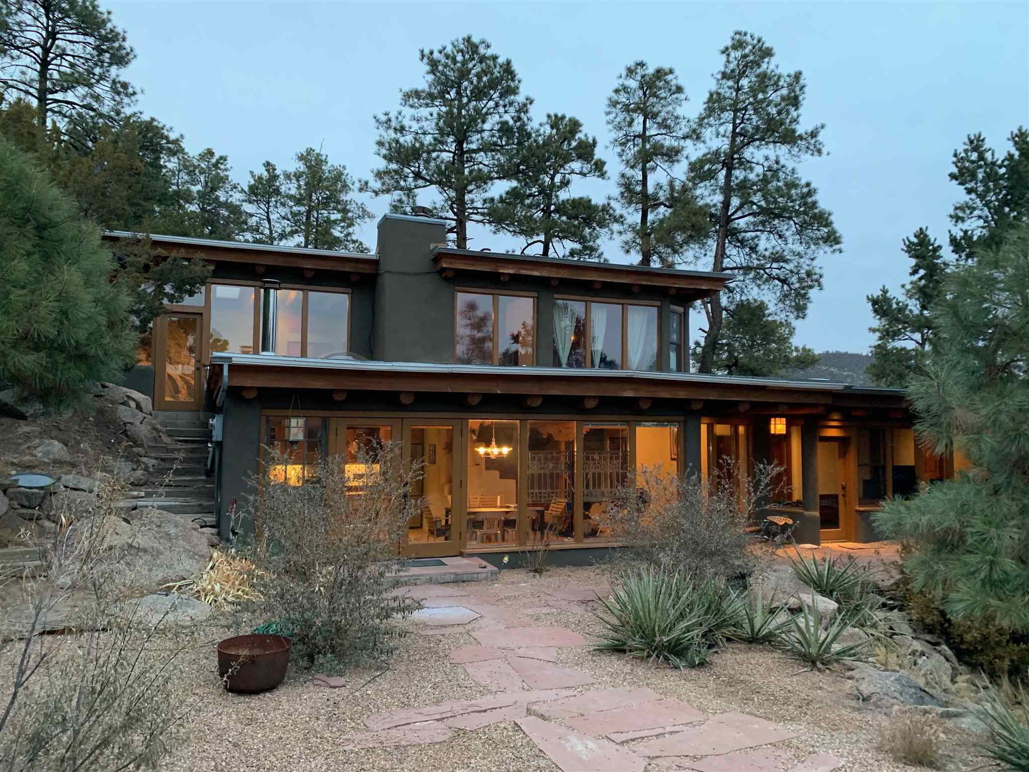 """A true mountain oasis minutes from town. This 4 bedroom / 2 bath main house and 1 bedroom / 1 bath guest house sits high above the valley on a Ponderosa Pine filled 2.74 acre lot overlooking national forest. The main house has a large kitchen / living area downstairs with custom concrete counters inlayed with turquoise and stainless steel appliances. In addition to electric baseboard heat, the main floor also has a large wood burning kiva fireplace and a wood burning stove to provide additional heat. There are two bedrooms on the first floor with a shared full bath. Upstairs has a third guest room built around the existing granite along with a full master bath and master bedroom.  A huge deck extends from the master bedroom around the north side of the house with views of the surrounding pine covered hills.  The guest house, almost completely out of sight from the main house, has a full kitchen and sitting area downstairs with a large bedroom and bath upstairs. Both levels have exterior doors with a small patio off the bedroom. The home has four """"off street"""" parking spaces at the main house and two """"off street"""" spaces across the road from the guest house. There is also an a LARGE storage shed included on the property in front of those two parking spaces."""