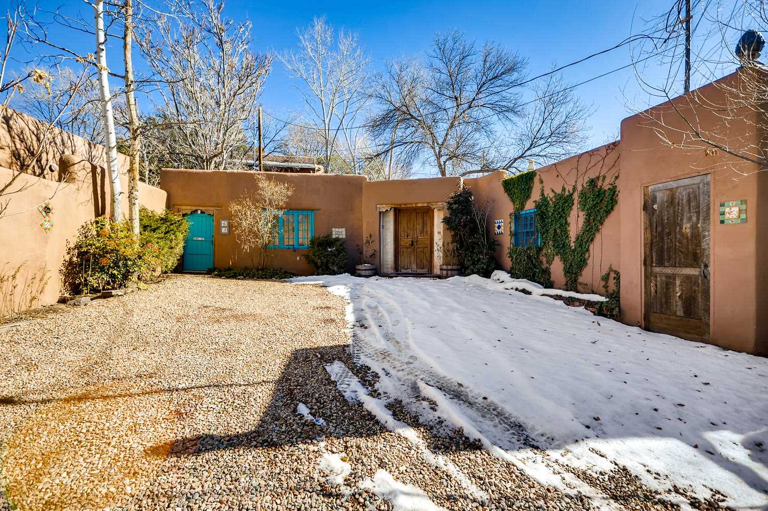 This quintessential Santa Fe Property awaits the creative touches of a new owner.  Located in the historic Eastside, it is a classic estate - the main house with a European feel, a guest house that will make you smile and a free-standing chapel.  The main house is flooded with light from the walls of windows and french doors, and wraps around the interior courtyard, featuring a flagstone patio and tiled fountain.  The guest house includes a striking tiled bath, its own living/dining area, kitchen, and a rare basement that includes a laundry.  The property is accented with a collection of tiles from all over the world.