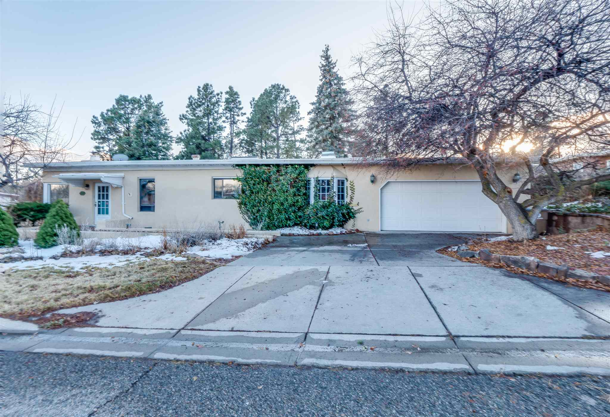 Wow! Western area convenience, landscaped backyard oasis on .35ac lot, and tons of character in this spacious single-level home! Enjoy Jemez mountain views as you arrive at this welcoming home in the perfect central location. Walk into a beautiful front living room with gorgeous beamed wood ceiling, wood flooring, and corner windows all accented by a cozy wood burning fireplace. Adjoining formal dining area has neat built-ins for display and is a light and open space for gathering. The kitchen offers bright tile accents, Saltillo tile floors, butcher block counter area, huge pantry, and window overlooking the front. On one side, the kitchen connects to an awesome mudroom directly off the attached 2-car garage and laundry space which connects to the back of the home. Heading through from the dining and kitchen the other way leads to a neat full guest bath, and much more living space. From here the possibilities are endless! Two more living spaces plus a bonus room with skylights, brick floor, gas stove, and two sets of french doors opening to a courtyard. The master wing, located on one side offers a walk-in closet, adjacent 3/4 bath, shelving, and storage. The other side of the home provides an inviting guest suite with beamed wood ceiling and 3/4 ensuite. Enjoy easy access to the ice rink and Pajarito Mountain this winter and when spring arrives you'll be ready to enjoy wonderful perennial gardens throughout the backyard, tall pines, green grass, and tons of outdoor space!