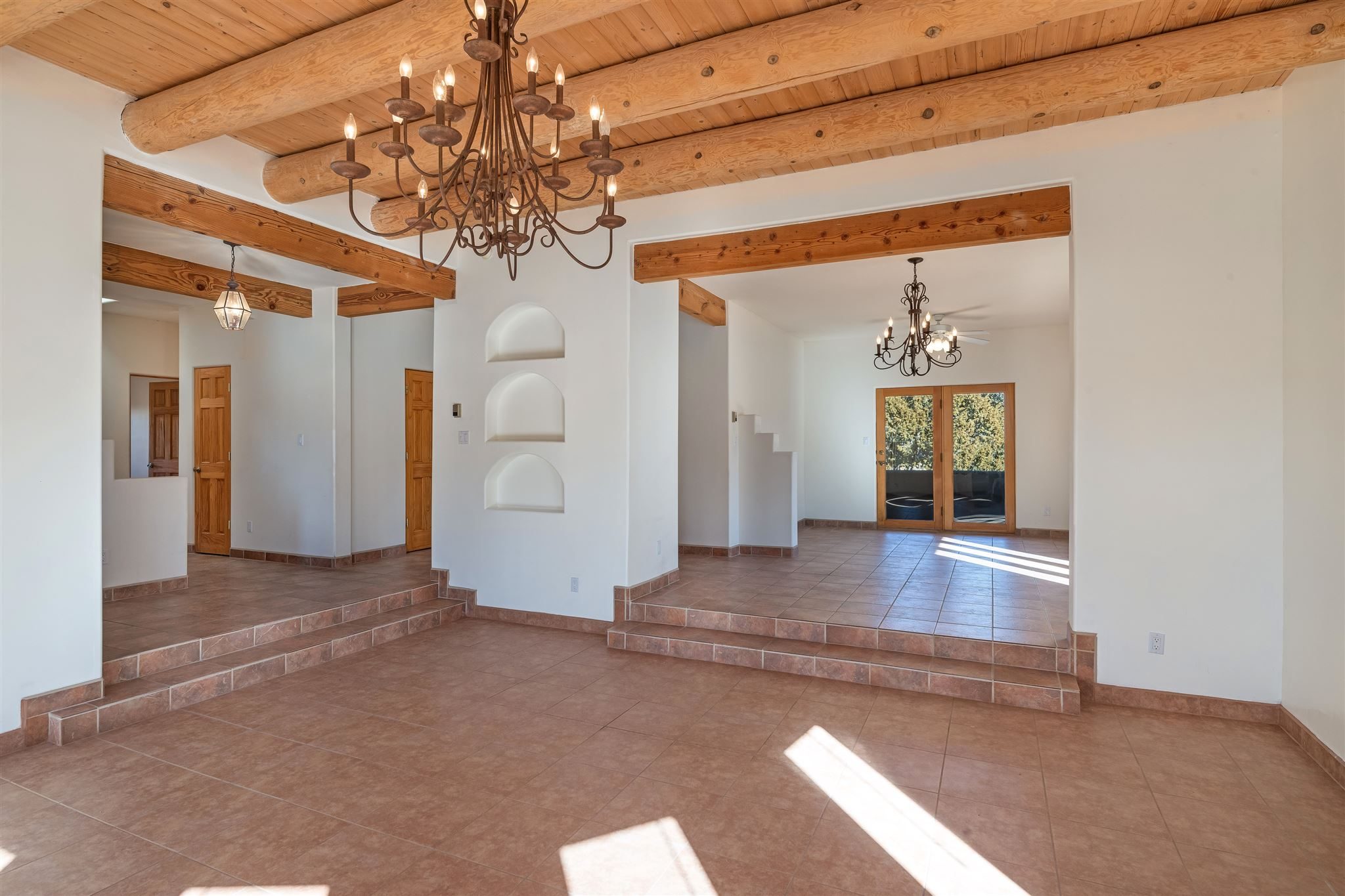Santa Fe Style, light filled home with big Sangre de Cristo Mountain views from your private back yard. Warm and inviting, this home enjoys large living spaces that flow easily between one another and the outdoors; a comfortable kitchen with pantry, dining room and great room, vigas and wood floors. The master bedroom is oversized, with a walk-in closet and spa bathroom. There are two additional bedrooms, a second bath and office area.  Enjoy the 2,269 square feet of living space with quality windows, skylights, radiant heat and much more! The finished 3 car garage with separate entrance allows for storage or hobbies.  You will love the being centrally located in the wonderful neighborhood.