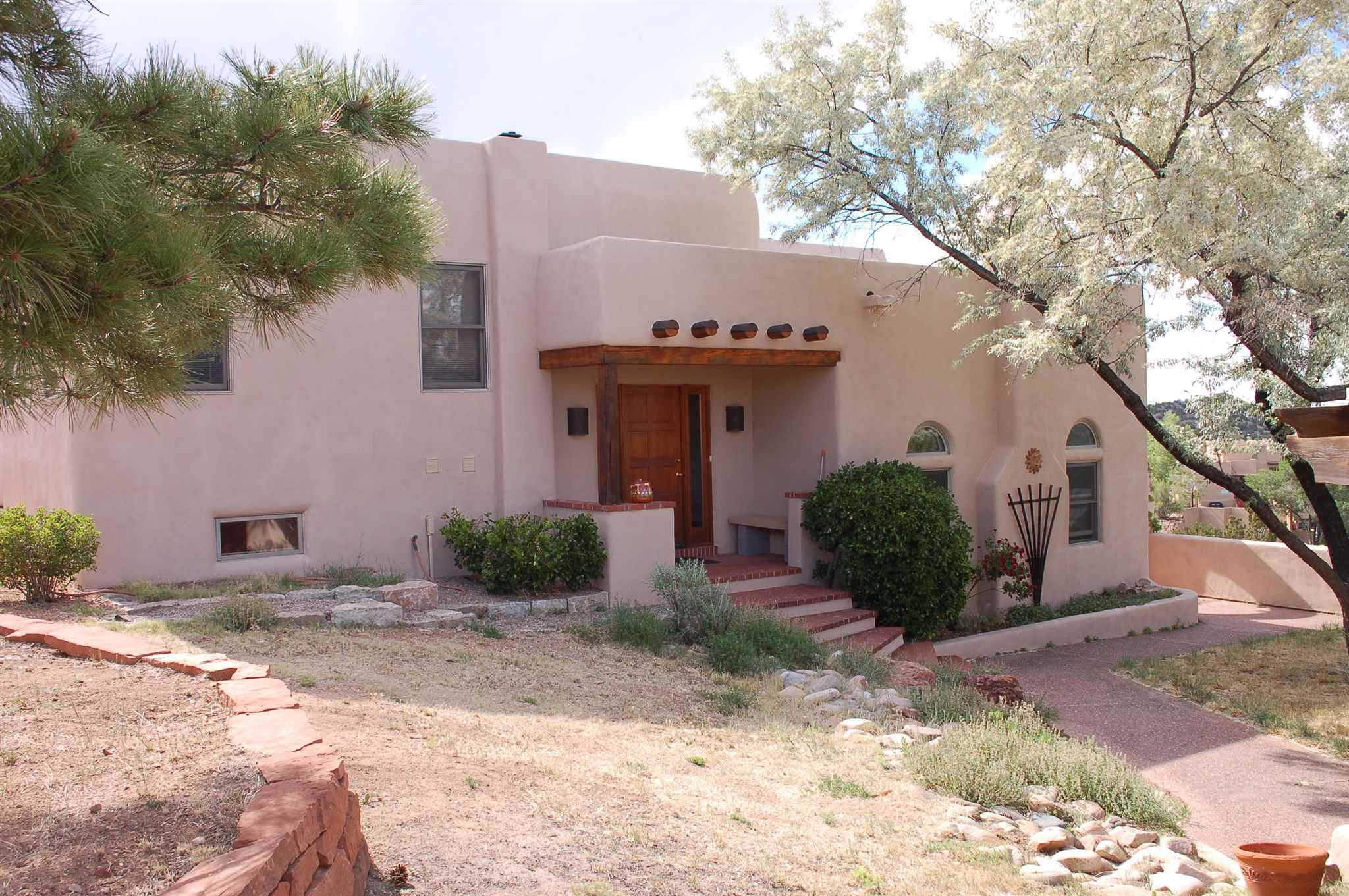 """Have the best of both worlds! Enjoy amazing sunsets and stunning mountain views on 5 private acres of country living only minutes to town. Three modern, energy efficient, multi-use structures include this custom, Santa Fe Pueblo style 3 Bedroom, 3 Bath home with office featuring vigas, beams, arched doorways throughout, Saltillo tile floors, and custom wood windows. The living room has 14 ft. high ceilings, a wood burning fireplace, and lighted nichos.  A rented guest house/casita with """"tenant in place"""" brings income as a bonus. In addition, is a detached heated over sized 2 car garage with storage and a heated studio/workshop (which can store more cars); perfect for the car enthusiast, artist, carpenter, or contractor. There is potentially parking up to 6 cars in the garage and studio, with up to 4 cars in the driveway. The master bedroom has a private view deck, beamed ceilings, fireplace, and built in bookshelves. The master bath has double sinks, and a 6 ft. Whirlpool tub for your complete relaxation. There is a steam shower, mud room, and separate laundry. Gardens of native landscaping are accented by rock, brick walkways and stucco walls. A 700 gallon rain water catchment system is connected to the garden water hydrant. This can also be a horse property for up to 4 horses so bring the horses. Convenient to 599 for Los Alamos commuters, shopping at the malls, and dining at Santa Fe's best restaurants."""