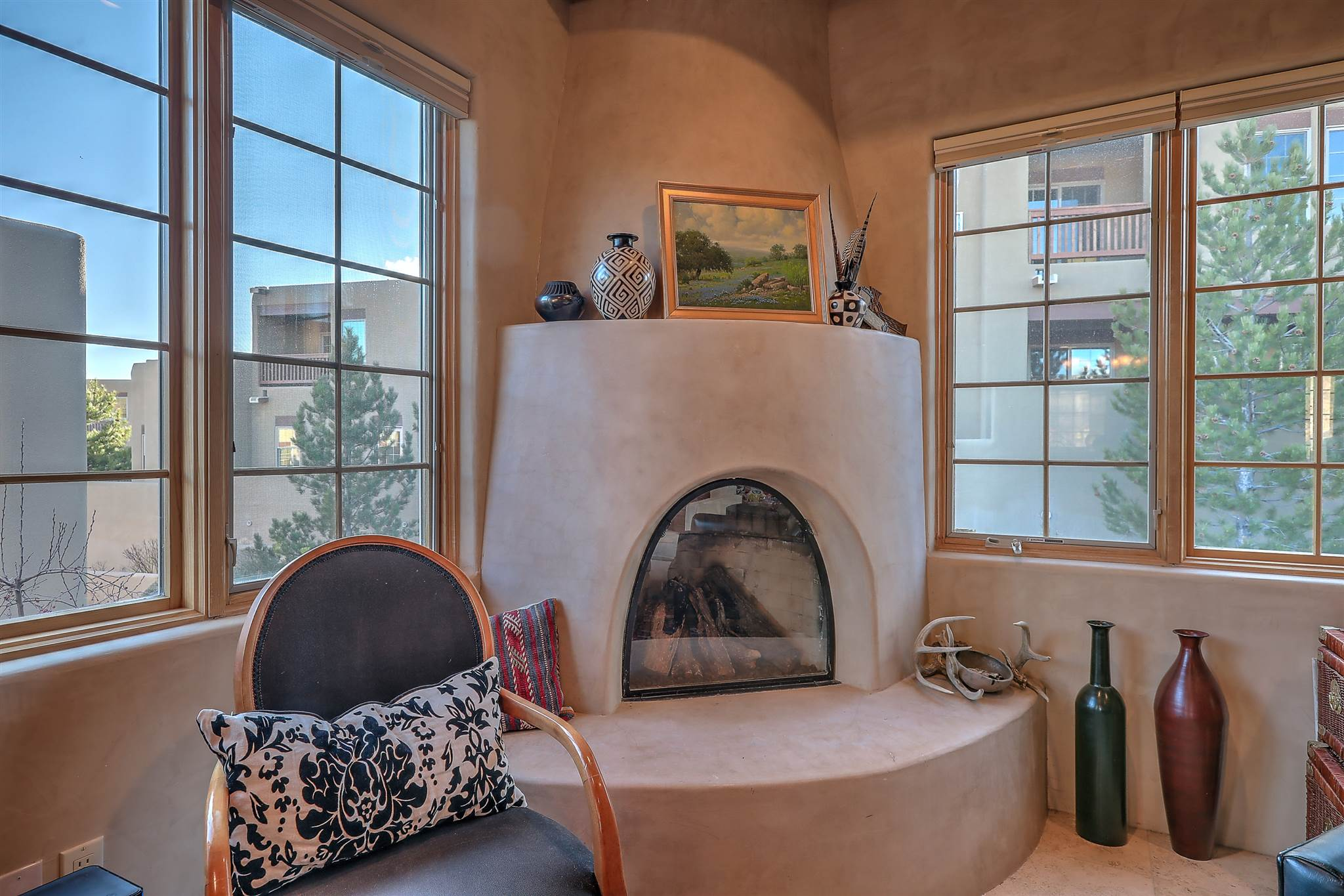 Hilltop Condo, walking distance to the Plaza from this Santa Fe two-story, two bedroom home with interior finishes of plastered walls, travertine floors, granite counters, and Jenn-Air appliances.  Vigas, nichos, and a gas kiva fireplace complement the second level.  Starry nights and open air views from larger deck are adjacent to the natural bio-diversity of Los Lovatos Arroyo.  Condo also has a smaller deck to the west and a Romeo and Juliet balcony to the south for plenty of fresh air and sunlight.  Property includes an attached one-car garage, stacked washer/dryer, with a roof-top heat-pump for forced air heat and AC.  Both bedrooms and two baths are at ground level. Vigas, nichos, and a gas kiva fireplace complement the upper level with kitchen, dining, and living rooms along with a half-bath.  Located just northeast of historic Santa Fe, the Rosario Hill Compound combines the pleasures of quiet, high-altitude, New Mexico living with the conveniences of location and proximity to museums, galleries, shops, and restaurants.  Nearby Fort Marcy Recreation Complex will offer a wide range of exercise facilities and fitness classes.  This hilltop location in Rosario Hill Compound is close to historic venues of classical and contemporary music, dance, lectures, and international programs.