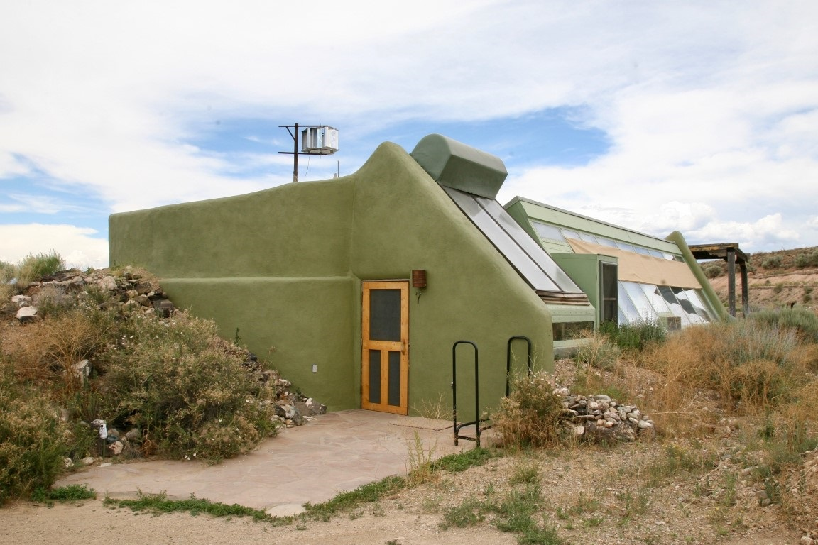 Enjoy complete Off-Grid living your beautiful 1200 sq.ft. studio Earthship. You have a bedroom/living room, 1 bathroom, full kitchen, patio& 1 car garage/laundry room. Close to Taos and the Ski Valley, with big sky nights. The upper portion of the lot would be a great place for a gazebo for 360 deg views of Taos Mesa. The Greater World Community also has 340 common acres of hiking trails and common space for community land owners. The community well provides water in dry years when catchment may be insufficient.