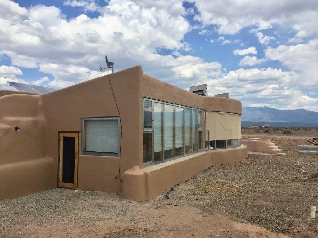 Enjoy complete Off-Grid living your beautiful 11537 sq.ft. studio Earthship. You have a 1 bedroom, living room, 1 bathroom, and full kitchen. Close to Taos and the Ski Valley, with big sky nights, and 360 degree views of Taos Mesa. The Greater World Community also has 340 common acres of hiking trails and common space for community land owners. The community well provides water in dry years when catchment may be insufficient.