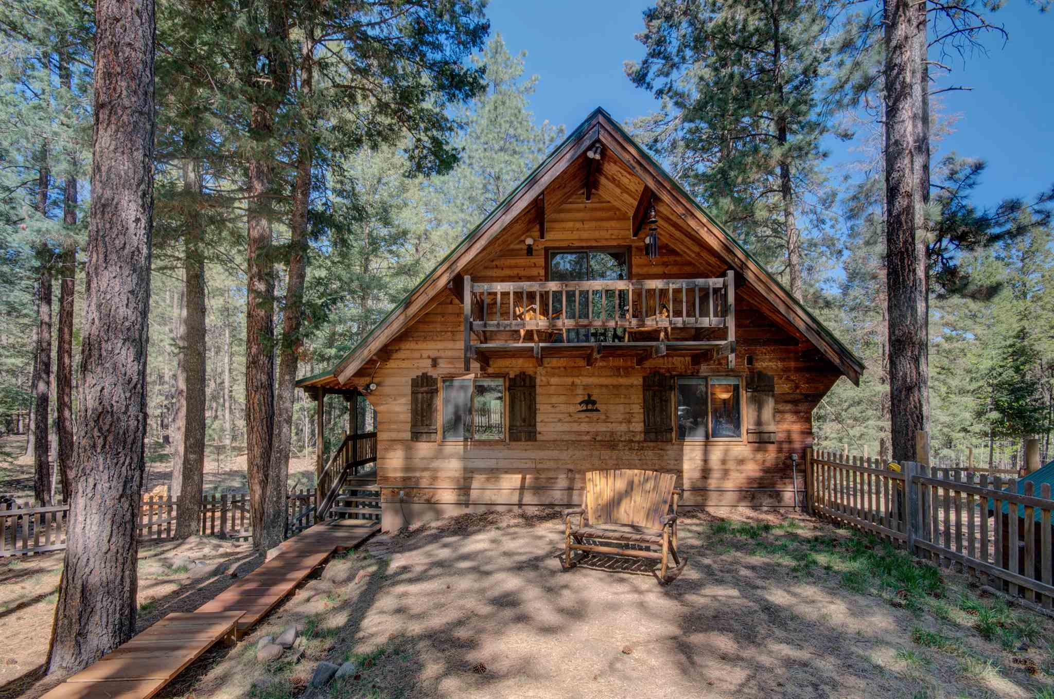 Endless panoramic views of pristine Mountain Forest from Hot tub on deck of this 3 Bedroom, 2 Bath, Log Home, Horse property! 2 story Greatroom wall of windows brings grandeur of Santa Fe National Forest into livingroom! Mudroom, finished basement, w/Gameroom, TV/Mediaroom, and huge Utility/Laundryroom, in 2400 Sq. Ft. Log Home. Chalet style 360 degree Fireplace w/rustic Blacksmiths Hood. Old West Tackroom/Feedbarn, HorseStall, Water tank, large Paddock/Pasture. Newer Roof. Newer Bosch Dishwasher. Newer Dekton Countertops in updated Kitchen. Newer Cast Iron Pellet Stove. Generac Generator wired to switch on. Spanish Corbeled Carport w/separate Quad cubby. Morgan Storage Building w/Shop bench. Driveway finished with gravel and a French drain. Picket Fenced front yard, w/Firepit & Benches, for S'mores! View of Redondo Peak. Hiking, fishing, snow sports, rock climbing, hot springs, Valles Caldera National Park all short drive away.  Easy 30 minute commute to Los Alamos.