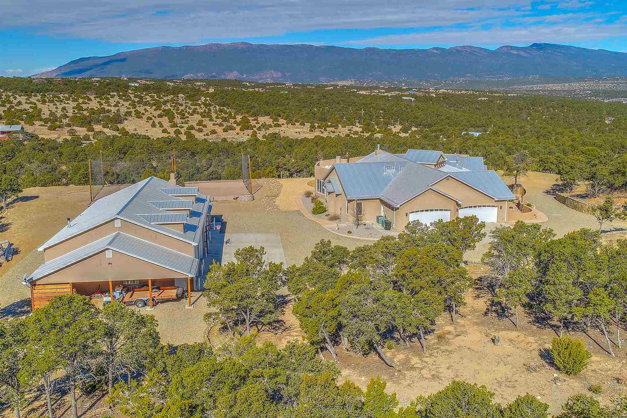 Spectacular views surround this exceptional custom home on 7 plus private acres just 25 minutes from ABQ international airport off of I-40. Hike, bike or ride your horse in the National forest. Main home with four bedrooms, three bathrooms, home office and wet-bar. Full Guest house and RV garage. Thermador appliances in a chef's kitchen with double ovens, 6-top gas stove, warming drawer and built-in refrigerator. Walk-in pantry and extensive cabinetry provide plenty of storage. Eat-in kitchen and breakfast bar as well as separate dining room for formal dinners. Bring the party outside to the extended patio, fire-pit, and volleyball court. Ambiance exudes throughout this high-end home including on-demand hot water, gas fireplaces, radiant floor heating and refrigerated air conditioning. Finished garage attached to main home with extended storage area. The guest house is fully equipped with kitchen, living area and fireplace. Attached workshop/garage is perfect for the car collector or hobbyist. A separate RV garage is attached to the workshop. Beautiful walled entry greets you at the electronic gated entry. Fully fenced.Year-round outdoor activities include hiking the National forest, netted outdoor sand volleyball, horse-shoes, greenhouse and endless spectacular views of sunsets.