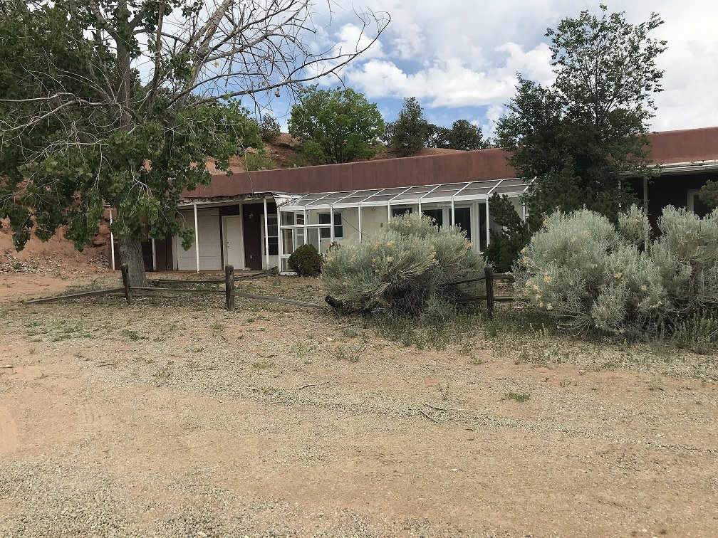 This 3 bedroom 2 bath home with a open sunroom across the front and nearly a whole acre lot, located near the center of Tesuque could be yours today, schedule your showing. Built into the hillside offering views of the beautiful valley below.