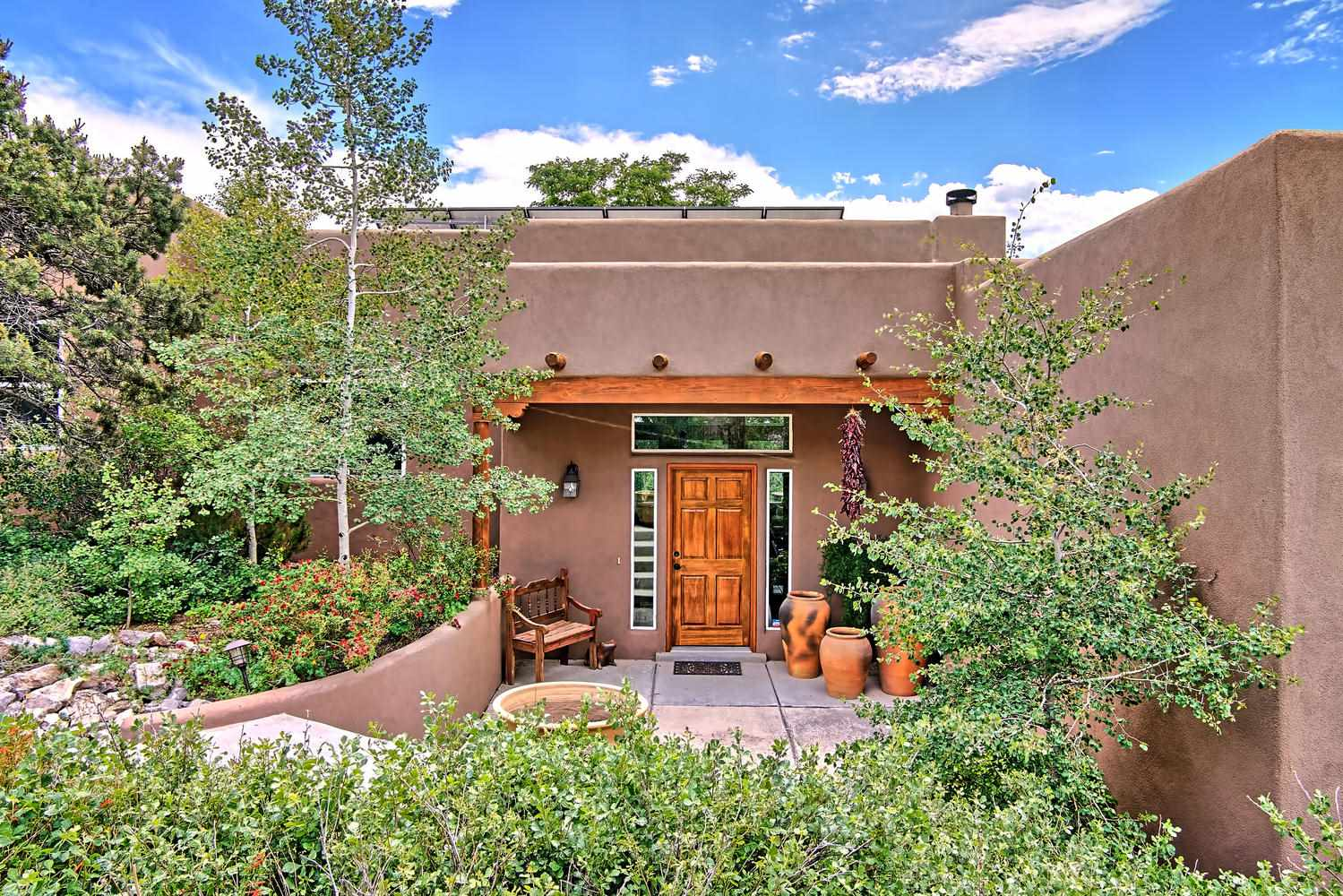 Thoughtfully planned to capture breathtaking Sandia Mountain vistas, this well-appointed Santa Fe-style home was custom built to reflect a warm, relaxing mountain ambience. Split-level design hugs the lay of the land and offers amenities galore*4 private outdoor living spaces*extensive gardens with a starburst of colorful flowers and shrubs plus their own quaint potting shed*Large windows, amazing light*Chef's-delight kitchen*Spacious sun-filled living area w/custom corner fireplace, raised tongue and groove ceilings*2205 heated sf detached workshop and studio is a perfect setting for a home-based business, telecommuting via high-speed communications, or a haven for creative pursuits*Newer, owned solar system*Experience Nature, peace of mind, and serenity. A slice of heaven.