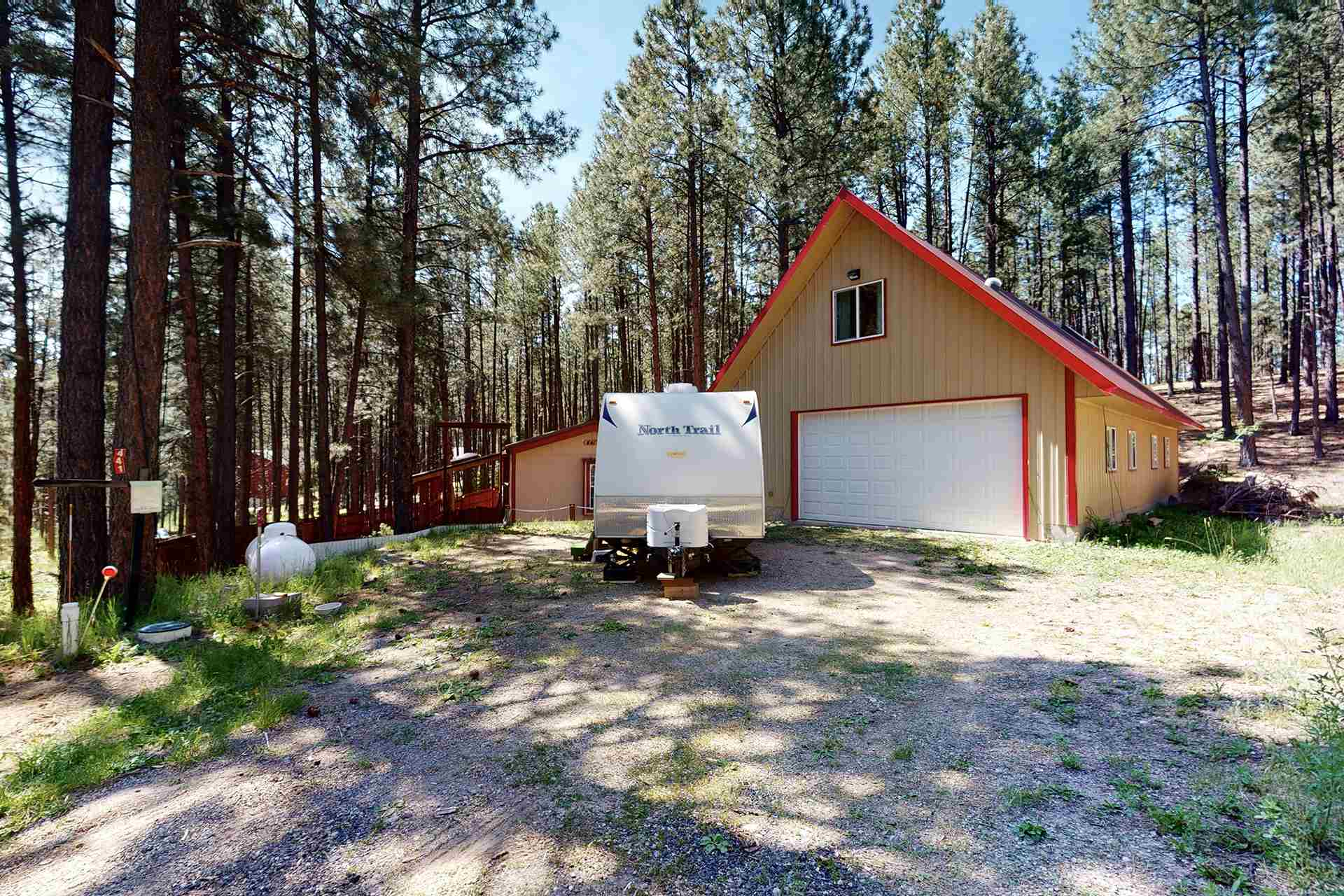 Are you looking for a place that provides serenity yet lots of activities close-by?  Look no further!  This home in Jemez Springs is literally a wildlife Mecca! Right down NM-4 you'll find Elk Viewing and Las Conchas Trail for hiking and viewing wildflower habitat!  Also right down NM 4 is the Valles Caldera National Preserve, a ski-walking area and the Bandelier National Monument. Now get ready to relax in your remodeled manufactured home sitting on a 1 acre lot.  Relax on the front Trex porch and enjoy the peacefulness.  Property Overview - Nicely remodeled manufactured home on a permanent foundation occupying 1 acre. New flooring. New kitchen cabinets and counter tops. Rustic tongue and groove wood in master bedroom. Master bath with double-headed shower and Jacuzzi bathtub New carpet in living area. Front and back covered Trex porches with skylights in front porch. 6ft cedar fenced yard. 4-bay 26 x 50 foot finished dream garage w/ versatile space on second floor for studio/office w/private balcony. Garage is plumbed, no winterization required, wet space is heated. Front and rear 10 x 16 roll-up garage doors (front is electric). Generator and fireplace in master bedroom do not convey.  Matterport Virtual Tour available under the photos section of the MLS.  Information on the HOA for Sierra Los Pinos/CCR's can be review at the following website: http://slppoa.org/www/policies